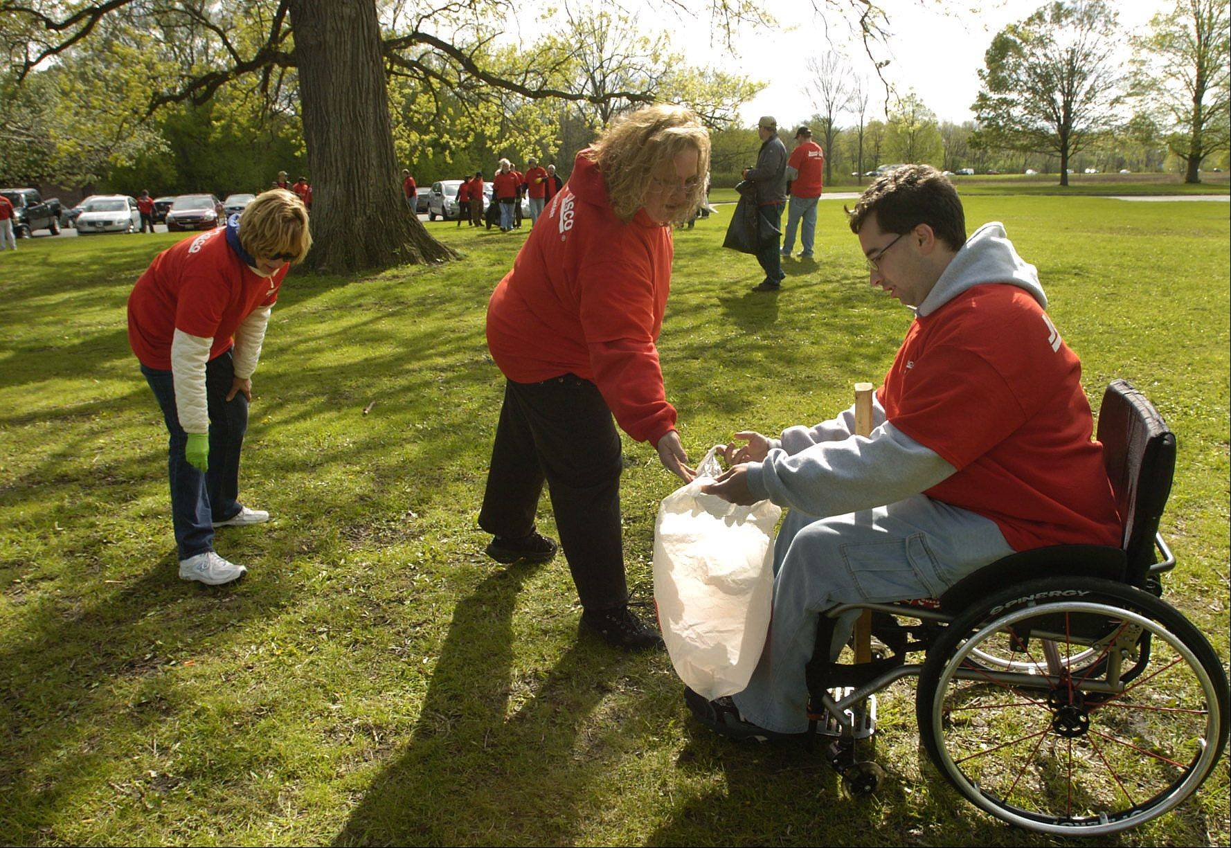Donna O'Connor of Wheeling, left, and Melissa Foreman of Buffalo Grove deposit refuse in the bag that Seth Goldberg of Arlington Heights holds, as Jewel/Osco employees participate in the 2012 Earth Day cleanup in Busse Woods.