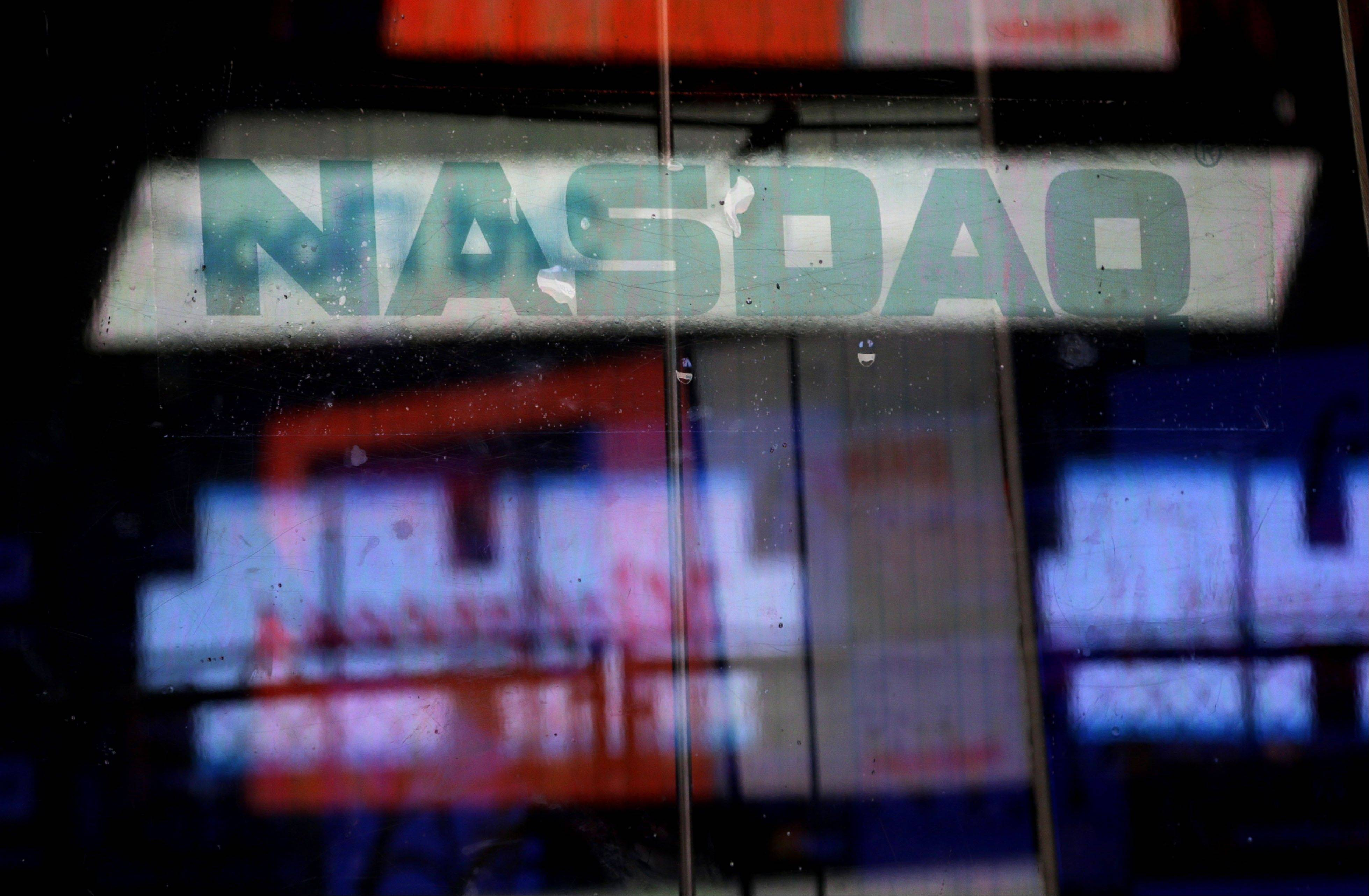 Electronic billboards are reflected in the windows of the Nasdaq in New York, where trading was halted Thursday because of a technical problem, the latest glitch to affect the stock market.