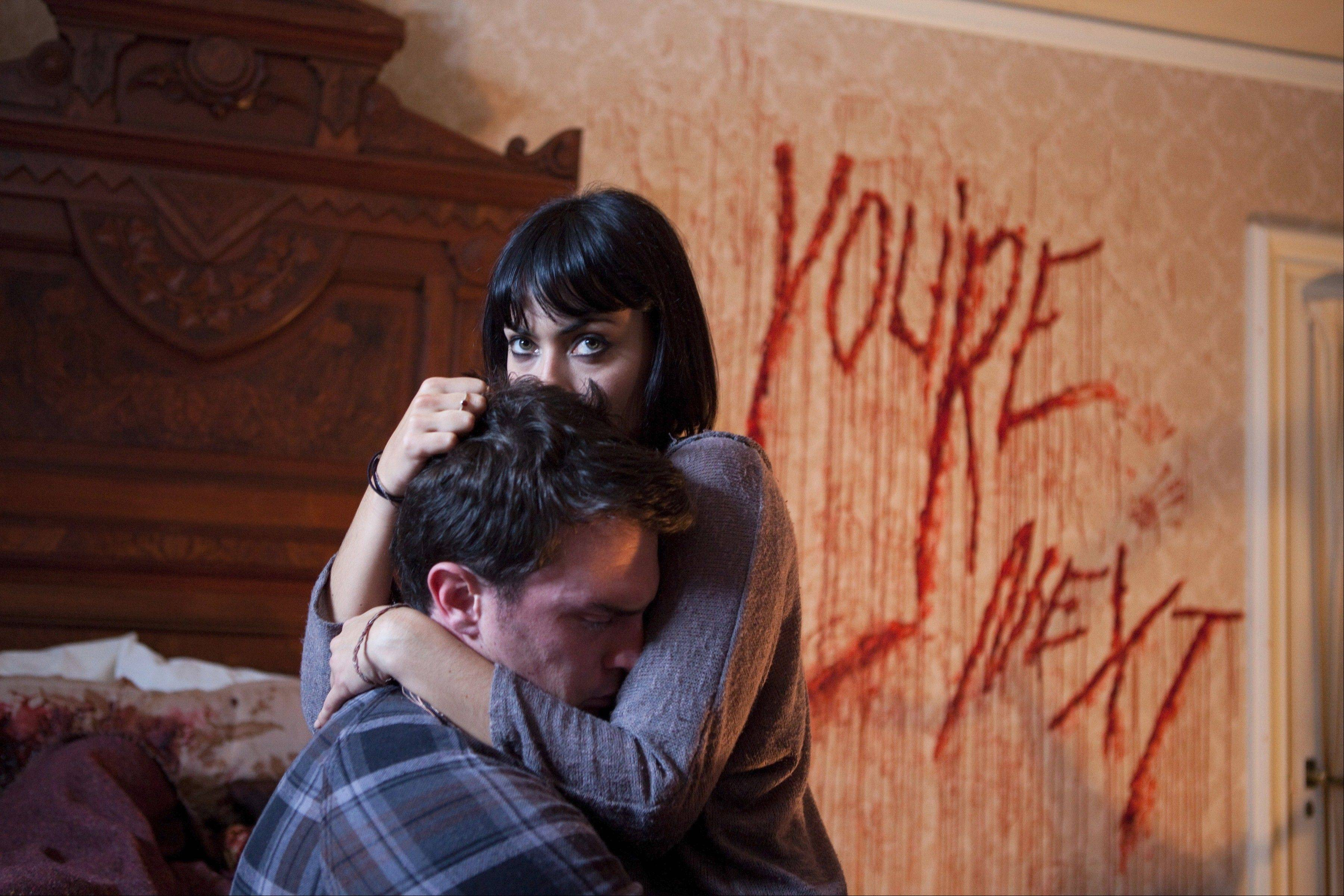 "Felix (Nick Tucci) and Zee (Wendy Glenn) cower in fear when a family reunion gets interrupted by homicidal animal masks in ""You're Next."""