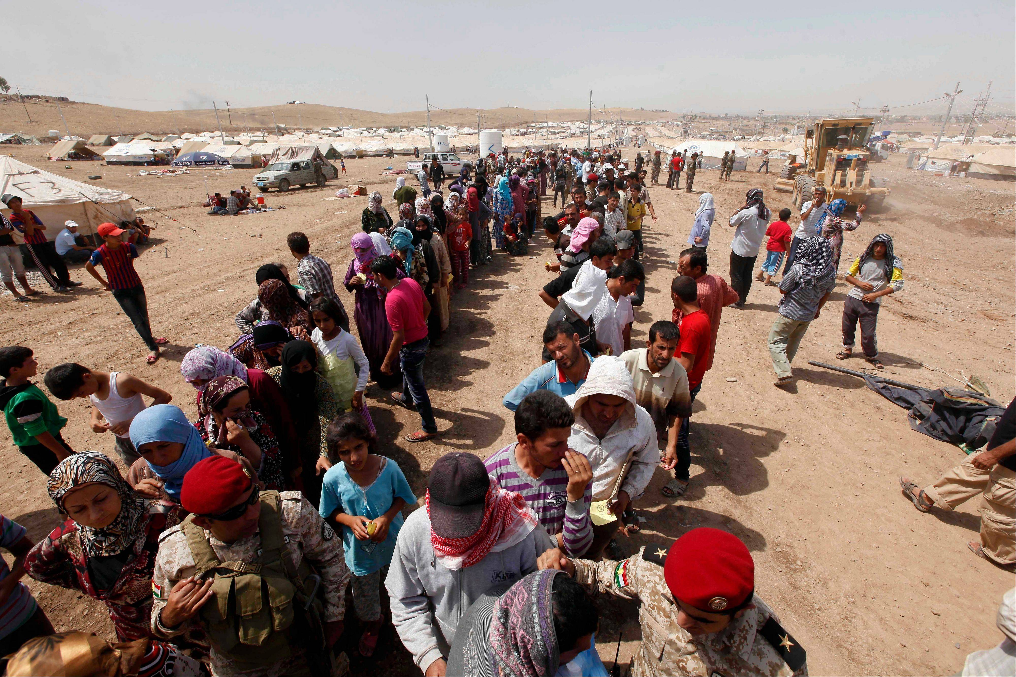 Syrian refugees gather for food aid at a camp 217 miles north of Baghdad, Iraq, Wednesday. Around 34,000 Syrians, the vast majority of them Kurds, have fled over a five-day stretch and crossed the border to the self-ruled Kurdish region of northern Iraq.