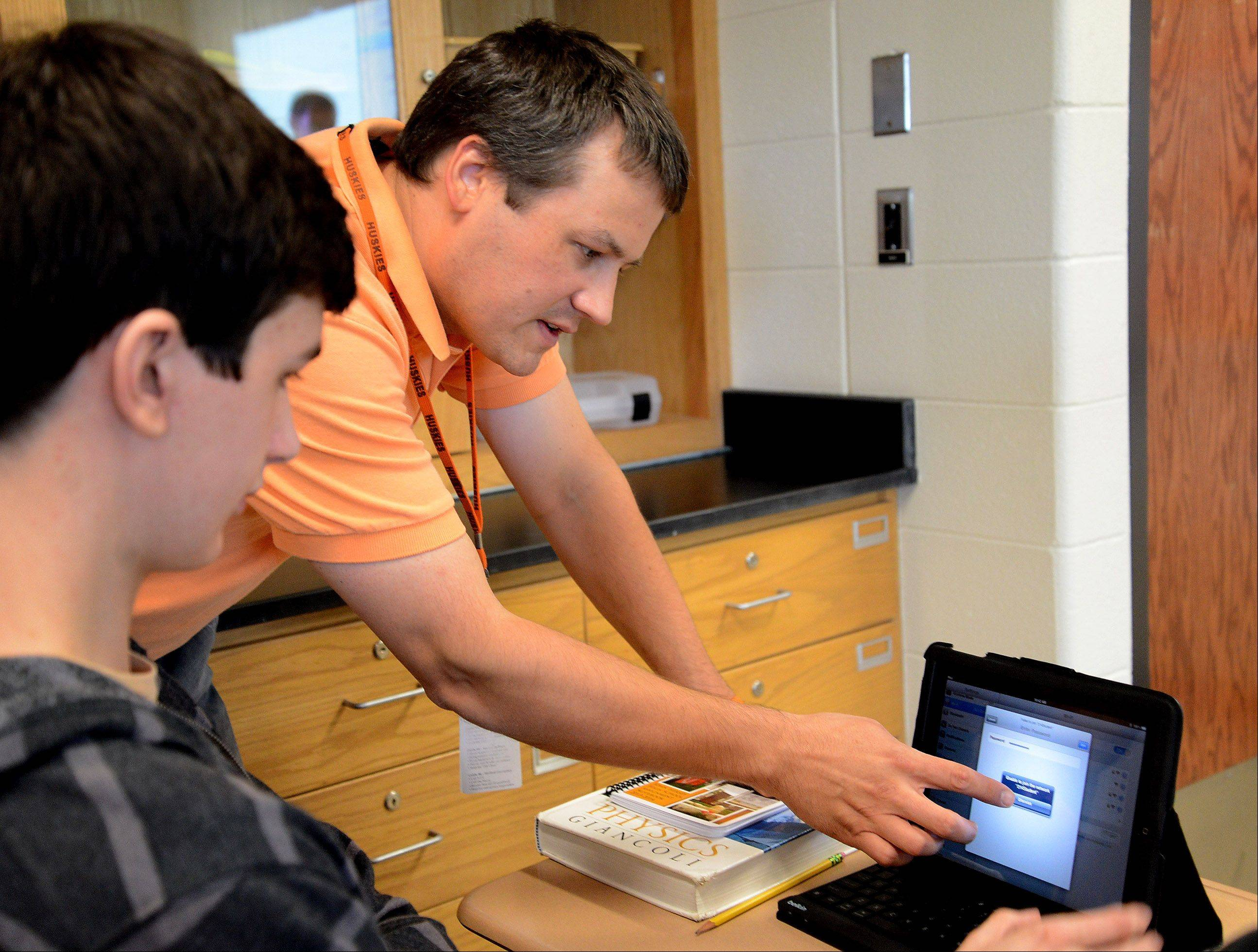 Honors physics teacher Jon Heintzelman helps Daniel Hansen log into his iPad Wednesday at Hersey High School. Northwest Suburban High School District 214 is among numerous suburban districts buying tablets for students.