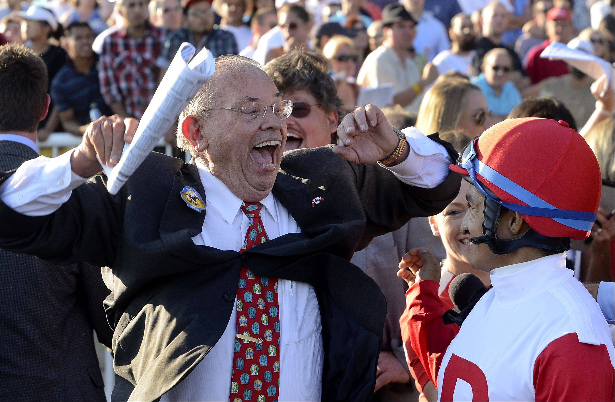 Real Solution owner Kenneth L. Ramsey celebrates with jockey Alan Garcia after being announced the winner of the 2013 Arlington Million.