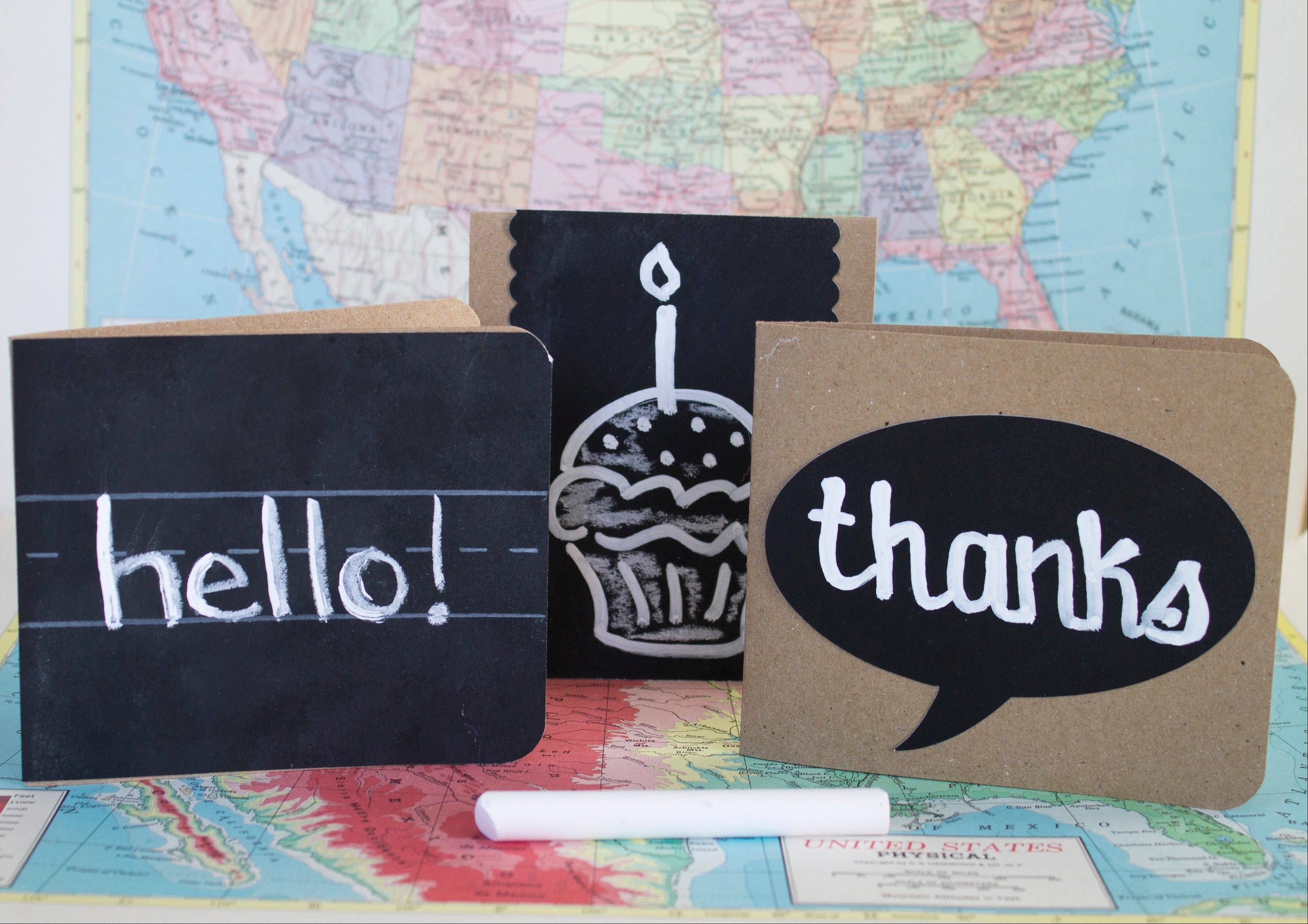 Handmade notecards are made by spraying cardstock with chalkboard paint. Get in the back-to-school mood by making notecards that incorporate old-school elements like chalkboards, vintage maps, notebook paper and brown paper lunch sacks.