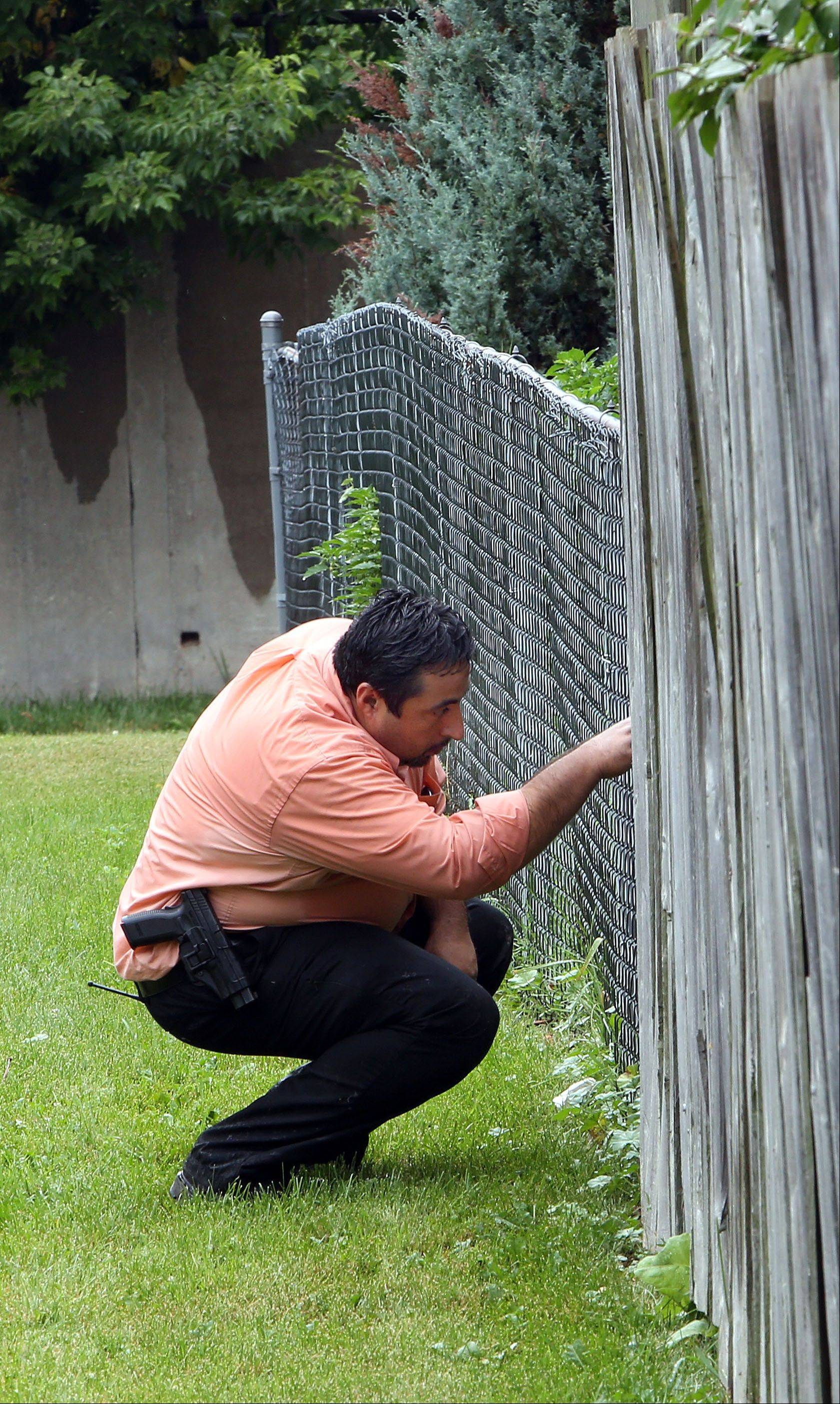 Zion police Officer Sabas Mercado looks through backyards on the 2300 block of Galilee Avenue for clues regarding the disappearance of 5-month-old Joshua Summeries, who went missing Wednesday.