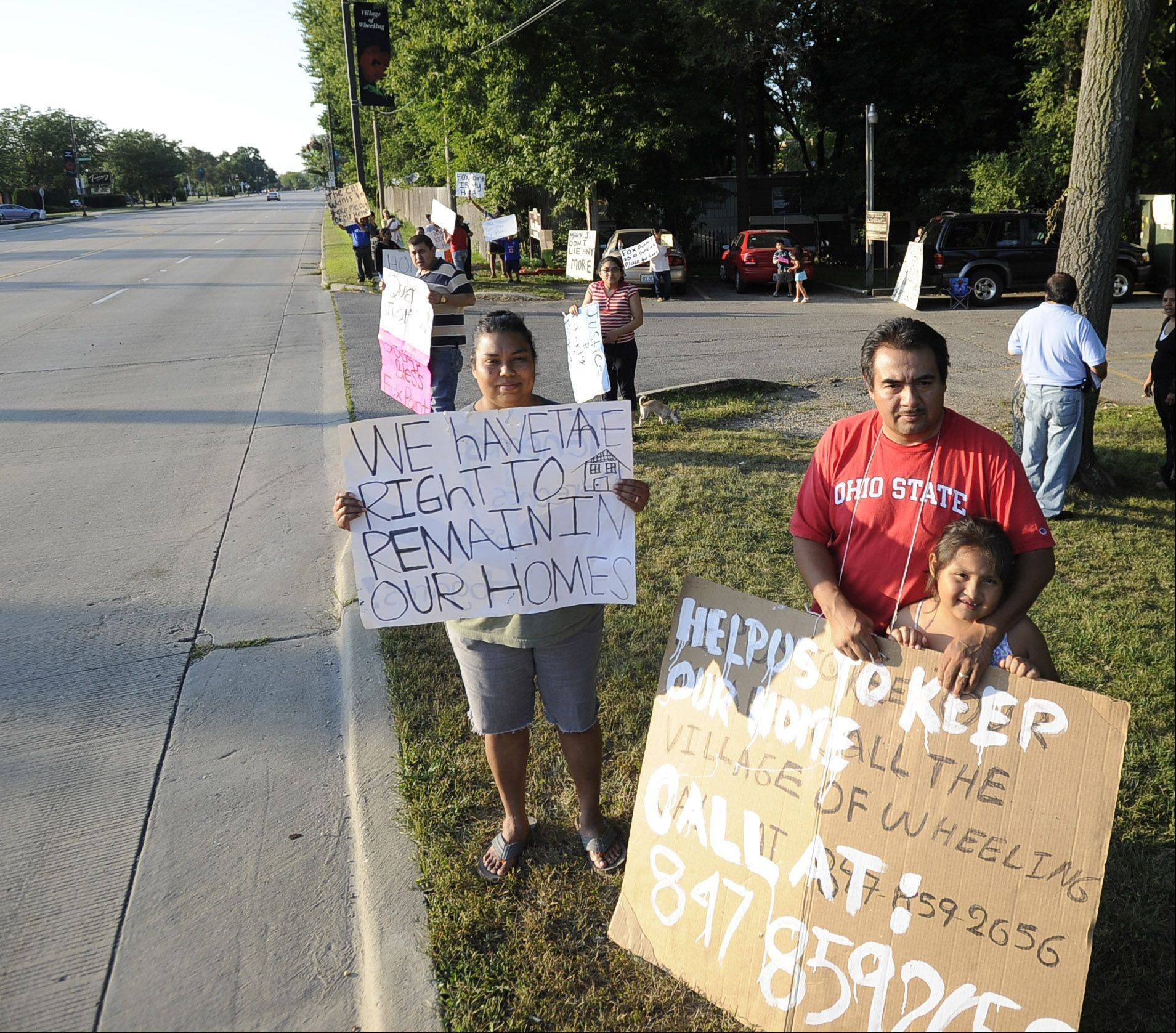 Cesar and Dases Cesles and his daughter Sarae, 7, protest what they say is Wheeling's attempt to drive out residents of Fox Point mobile home park along Milwaukee Avenue.