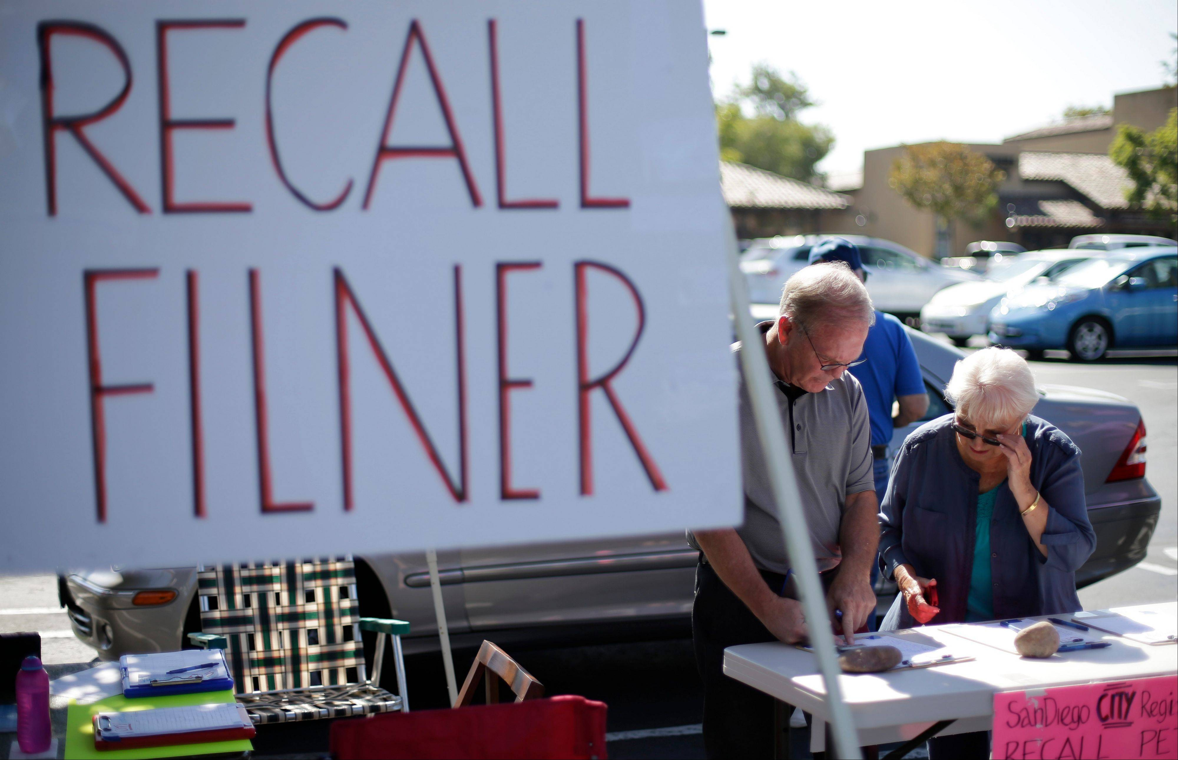Greg Timms, left, signs a petition to recall San Diego Mayor Bob Filner, alongside Tana Piontek, right, at a stand set up in the parking lot of a shopping center Wednesday, Aug. 21, 2013, in San Diego.