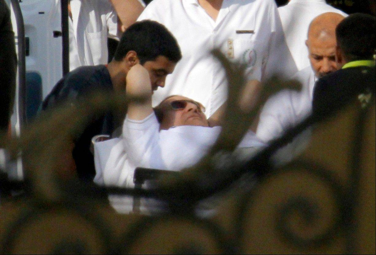 Egyptian medics escort former Egyptian President Hosni Mubarak, 85, into an ambulance after he was flown by a helicopter ambulance to a military hospital from Torah prison in Cairo Thursday.