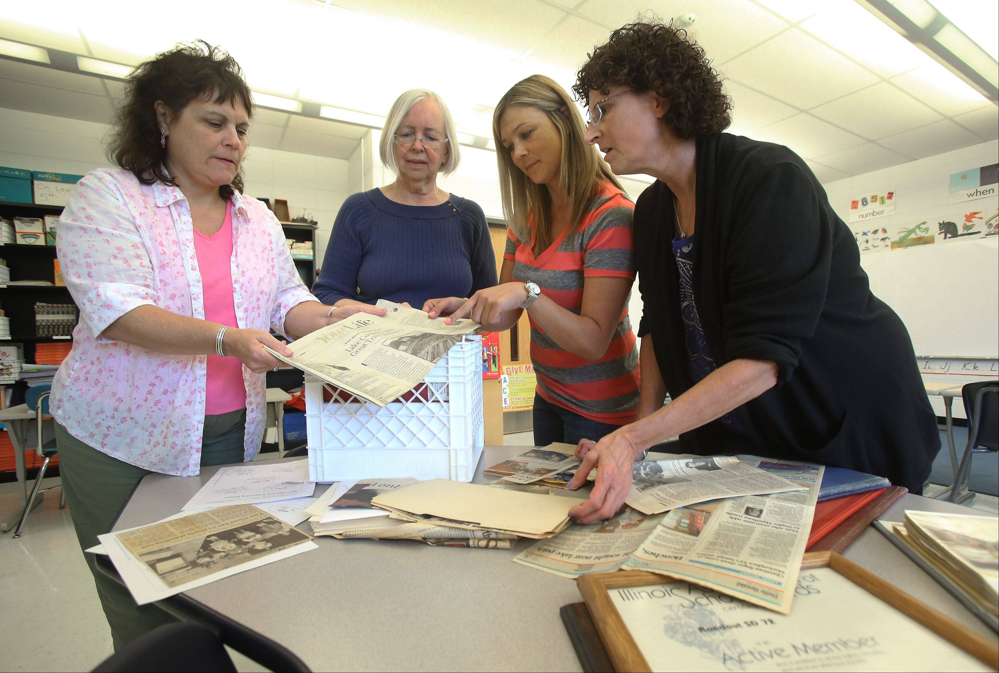 Rondout Elementary School staff members Vikki Paddock, left, Karen Farrell, Julie Fountas and Roxanne Greenberg review historical information Wednesday in preparation for the kickoff of the 150th anniversary activities.