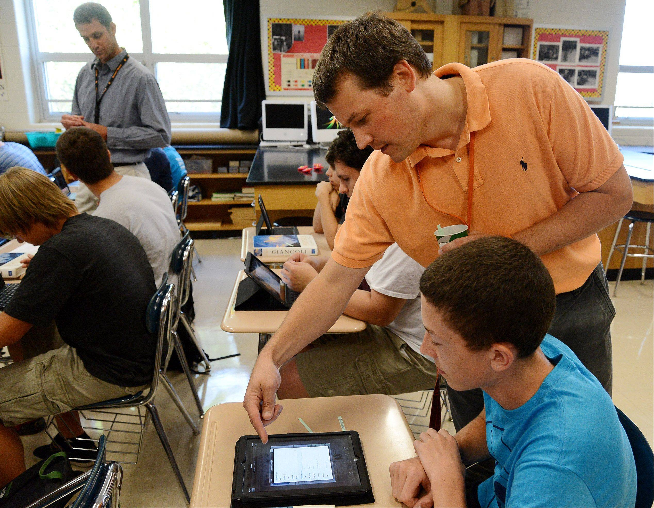 Honors physics teacher Jon Heintzelman helps Charlie Smith log into his iPad on the first day of classes at Hersey High School.