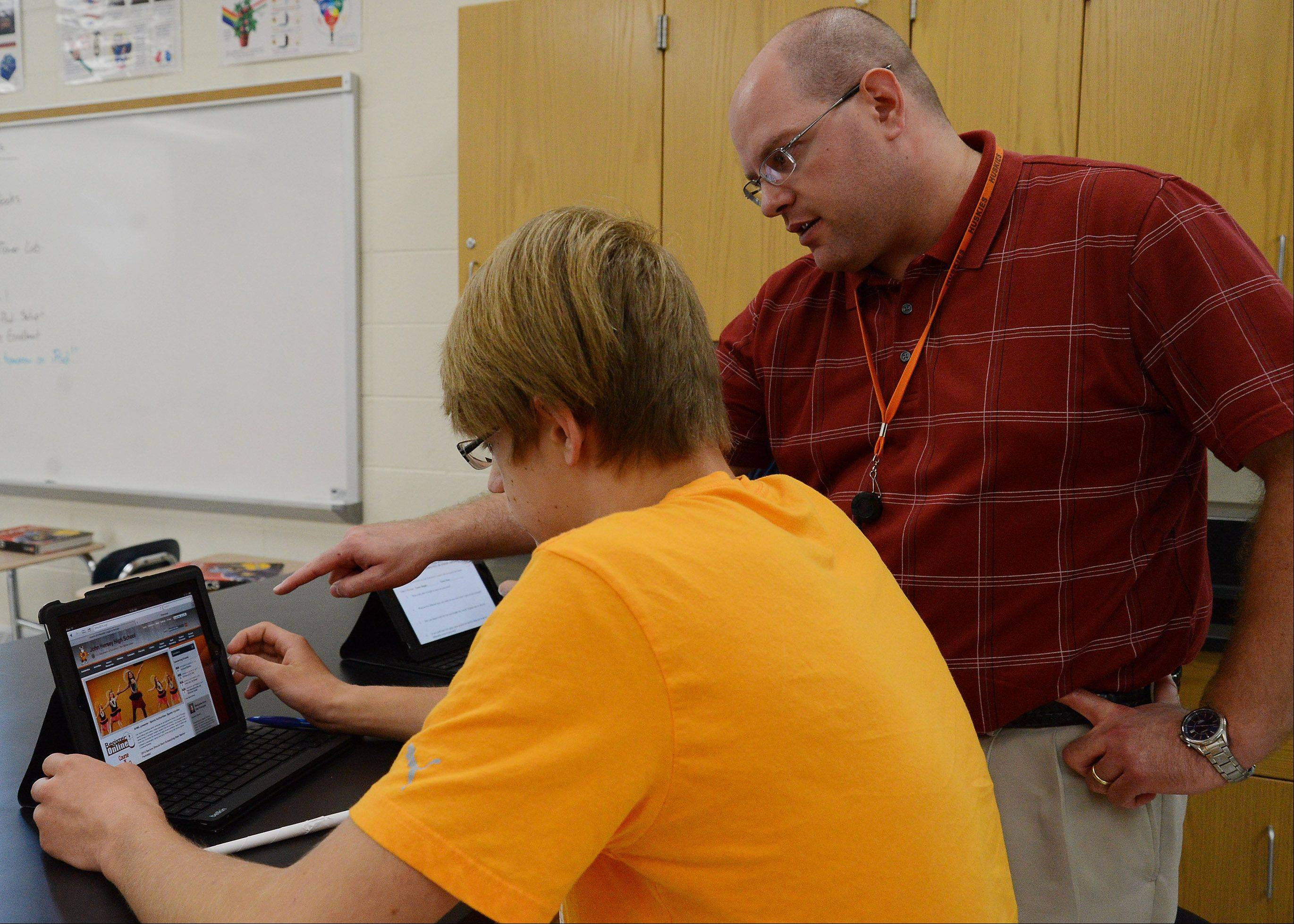 Hersey High School physics teacher Andy Finlayson instructs Danny Obyrtacz on how to use an iPad the student received as part of a pilot program.