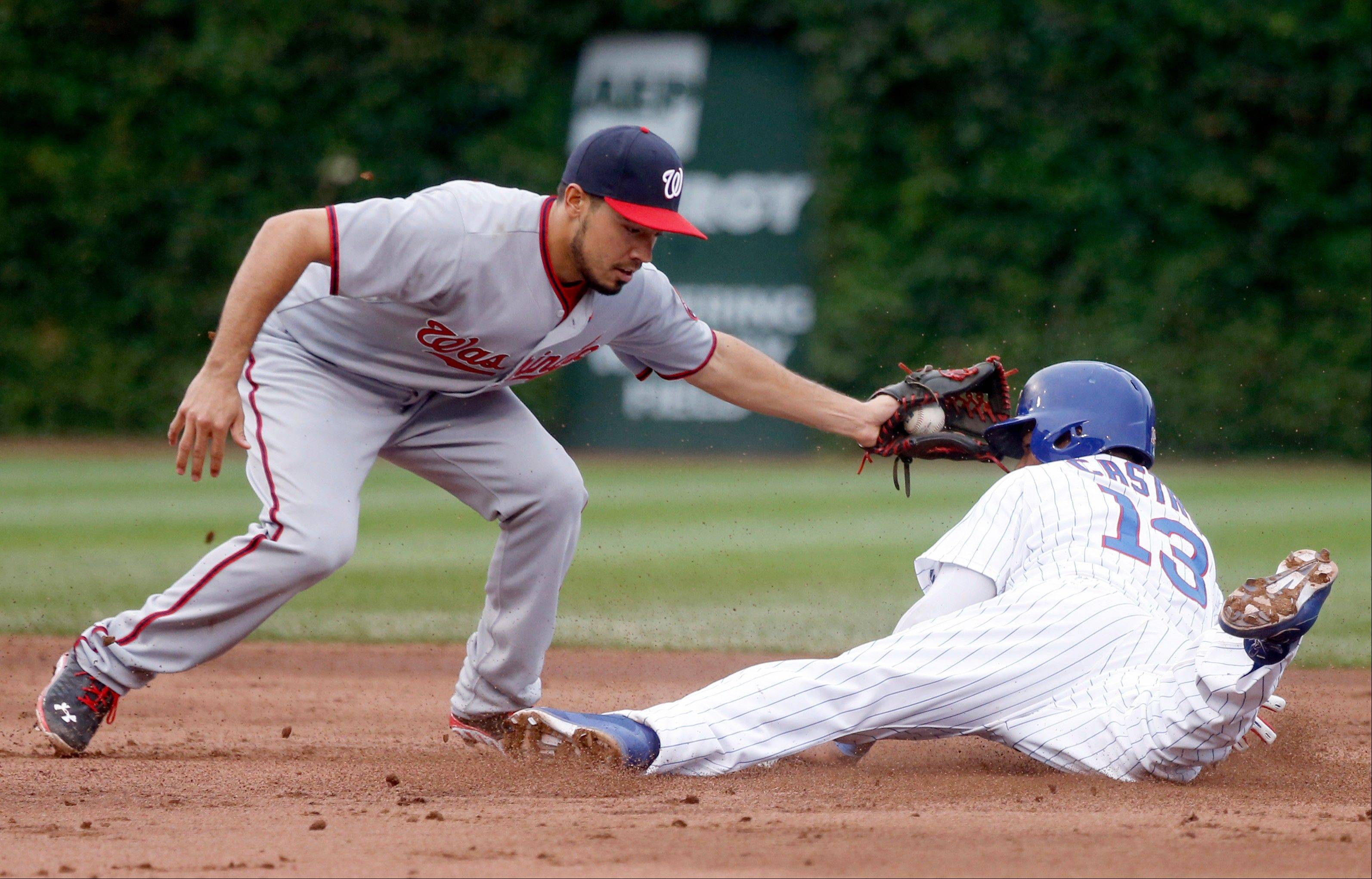 Washington Nationals second baseman Anthony Rendon, left, catches Chicago Cubs' Starlin Castro trying to steal second off a throw by catcher Wilson Ramos during the third inning of a baseball game on Thursday, Aug. 22, 2013, in Chicago.