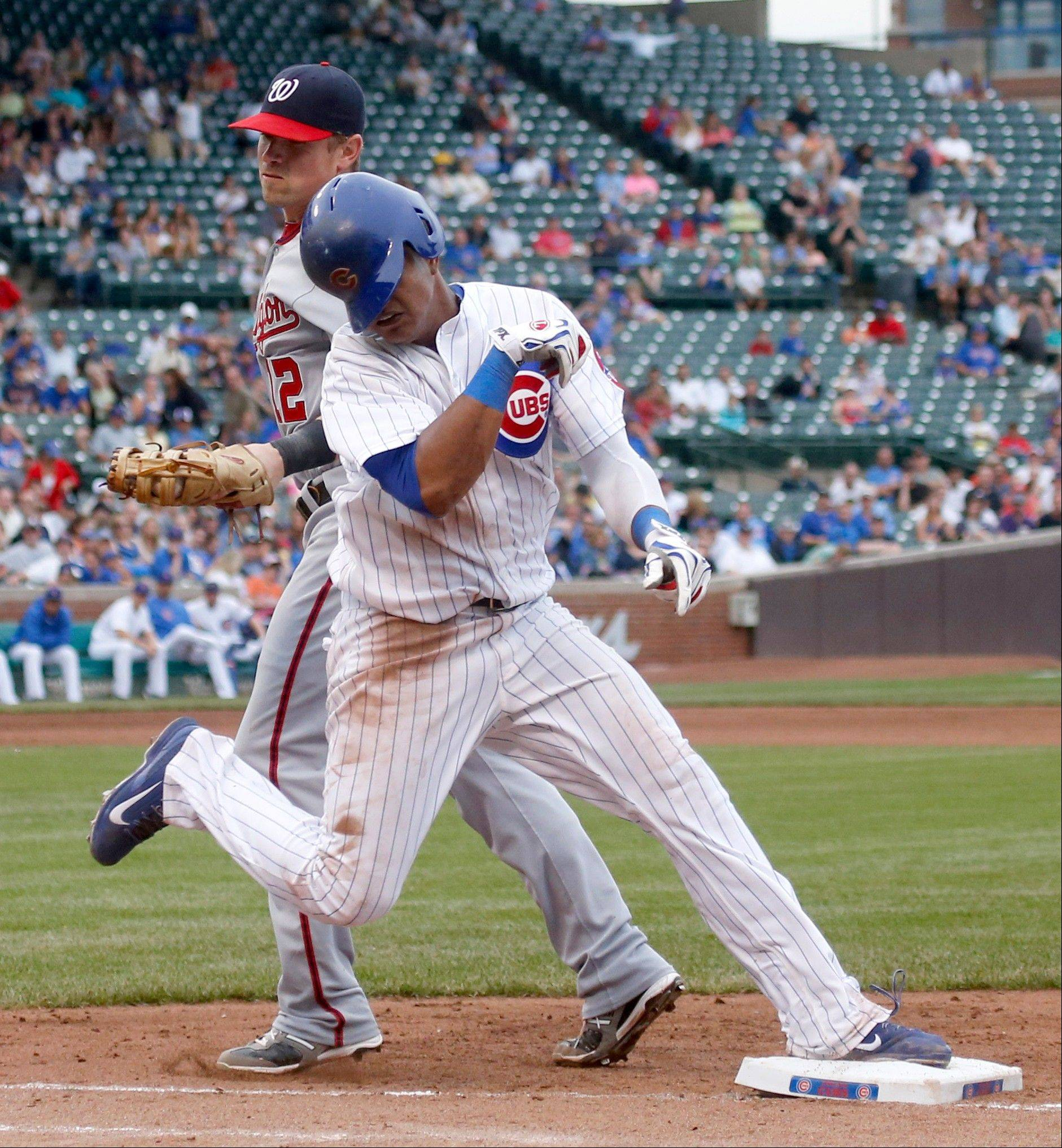 Chicago Cubs' Starlin Castro, right, is safe at first avoiding the tag by Washington Nationals first baseman Tyler Moore on a high throw by third baseman Ryan Zimmerman during the sixth inning of a baseball game Thursday, Aug. 22, 2013, in Chicago.