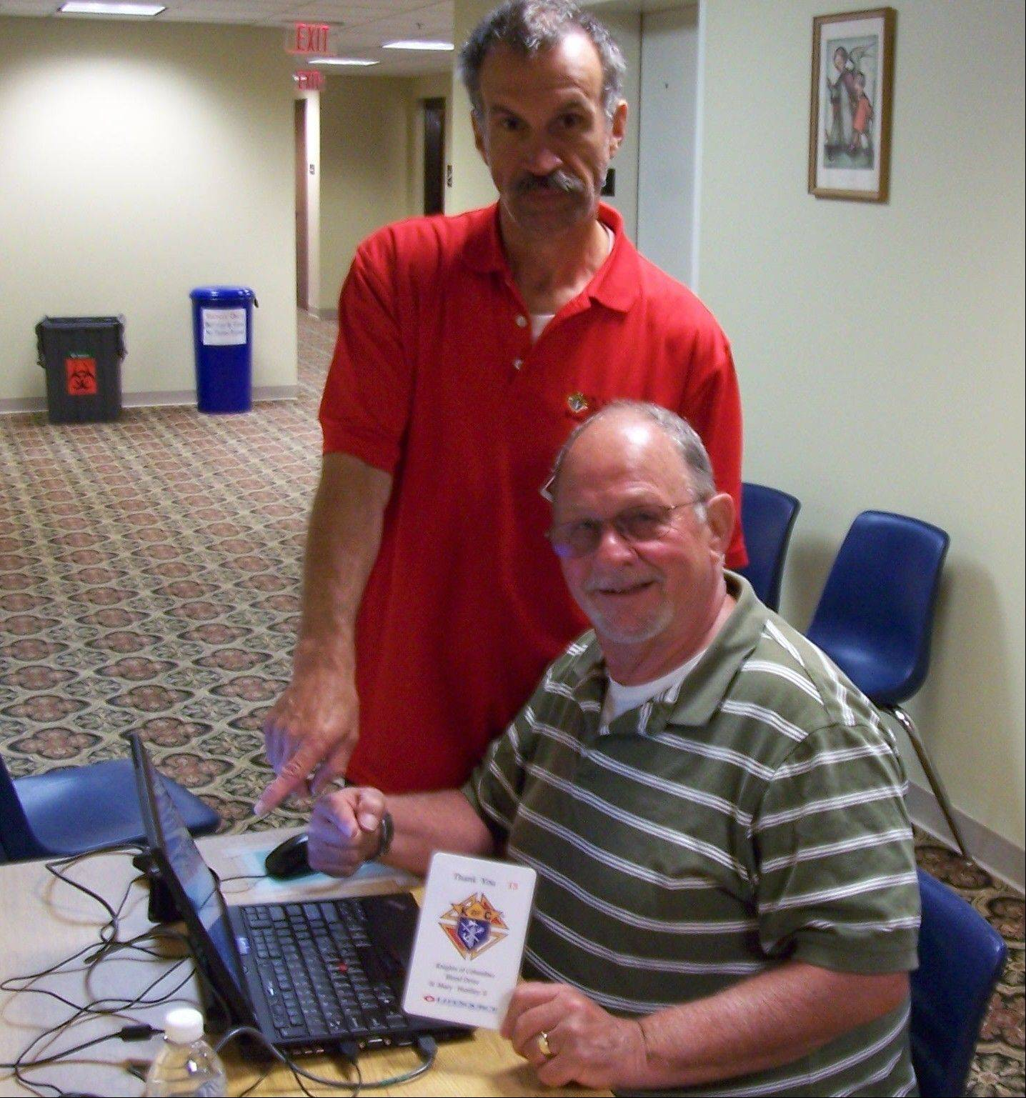 St. Mary Knight of Columbus member Phil Riccio, left, assists fellow member Keith Larsen in registering to donate blood. The quarterly blood drive was successful, with 71 units of blood donated.