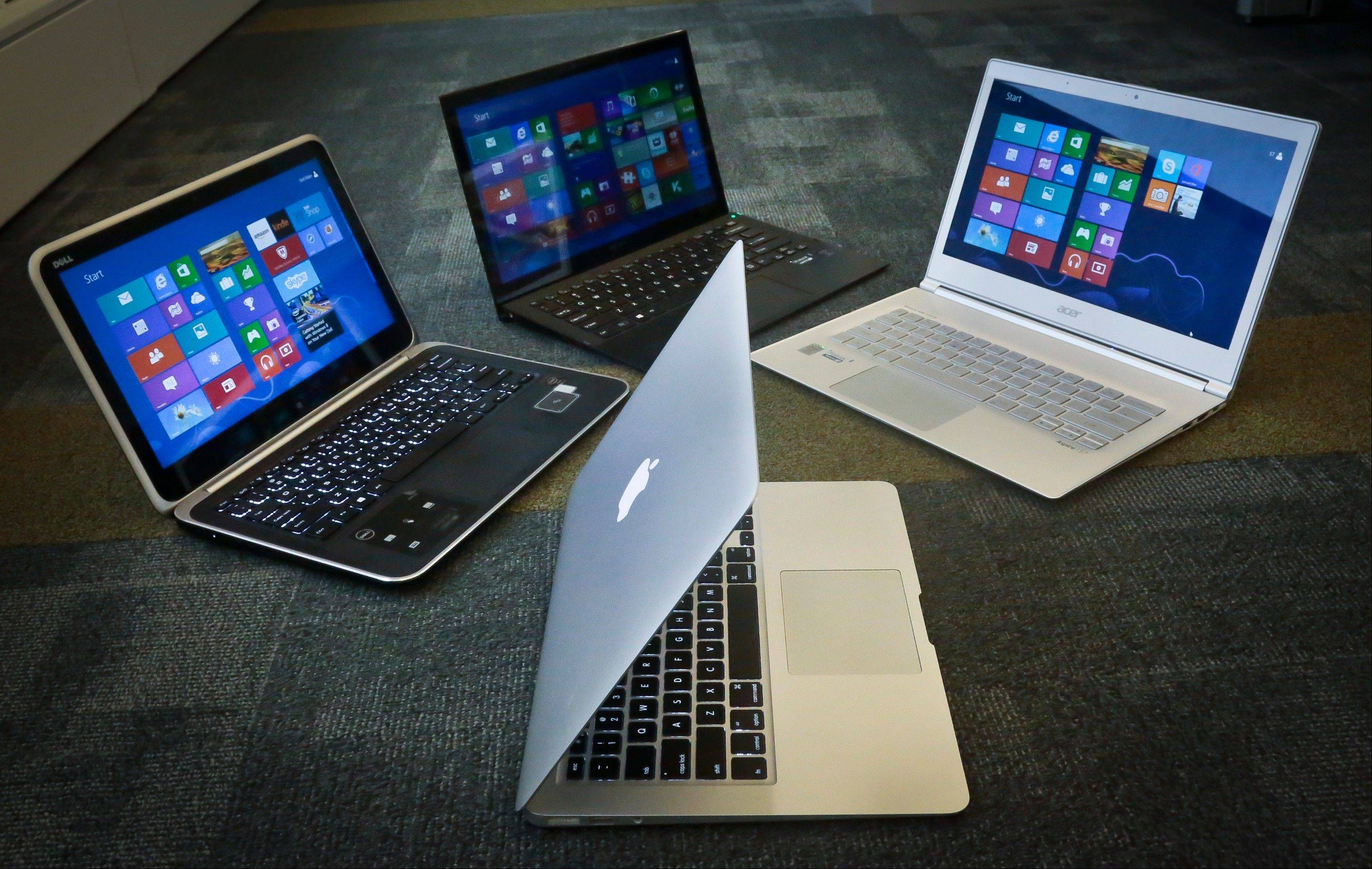 A MacBook Air from Apple, bottom center, a Vaio Pro 13 from Sony, top left, an Aspire S7 from Acer, center, and an XPS 12 from Dell, right. Best Buy is offering $100 off Apple iMacs and $20 off Beats headphones until Sept. 14.