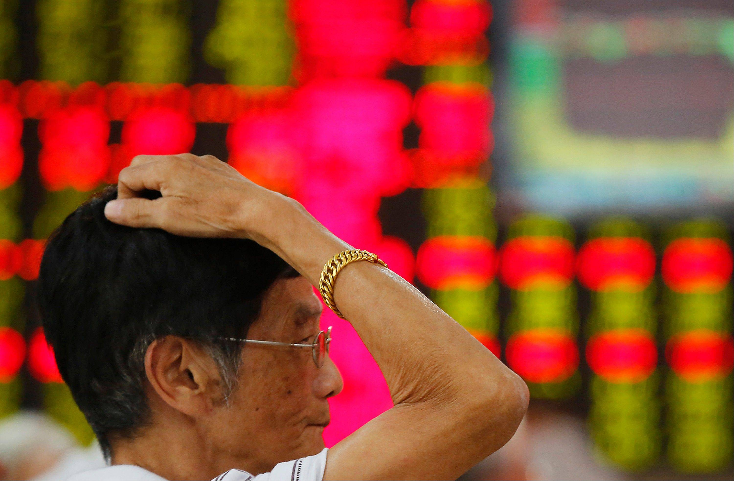 An investor looks at the stock price monitor Friday at a private securities company in Shanghai, China. Asian stock markets rose Friday after encouraging economic data from China and Europe raised hopes that a global economic recovery was under way.