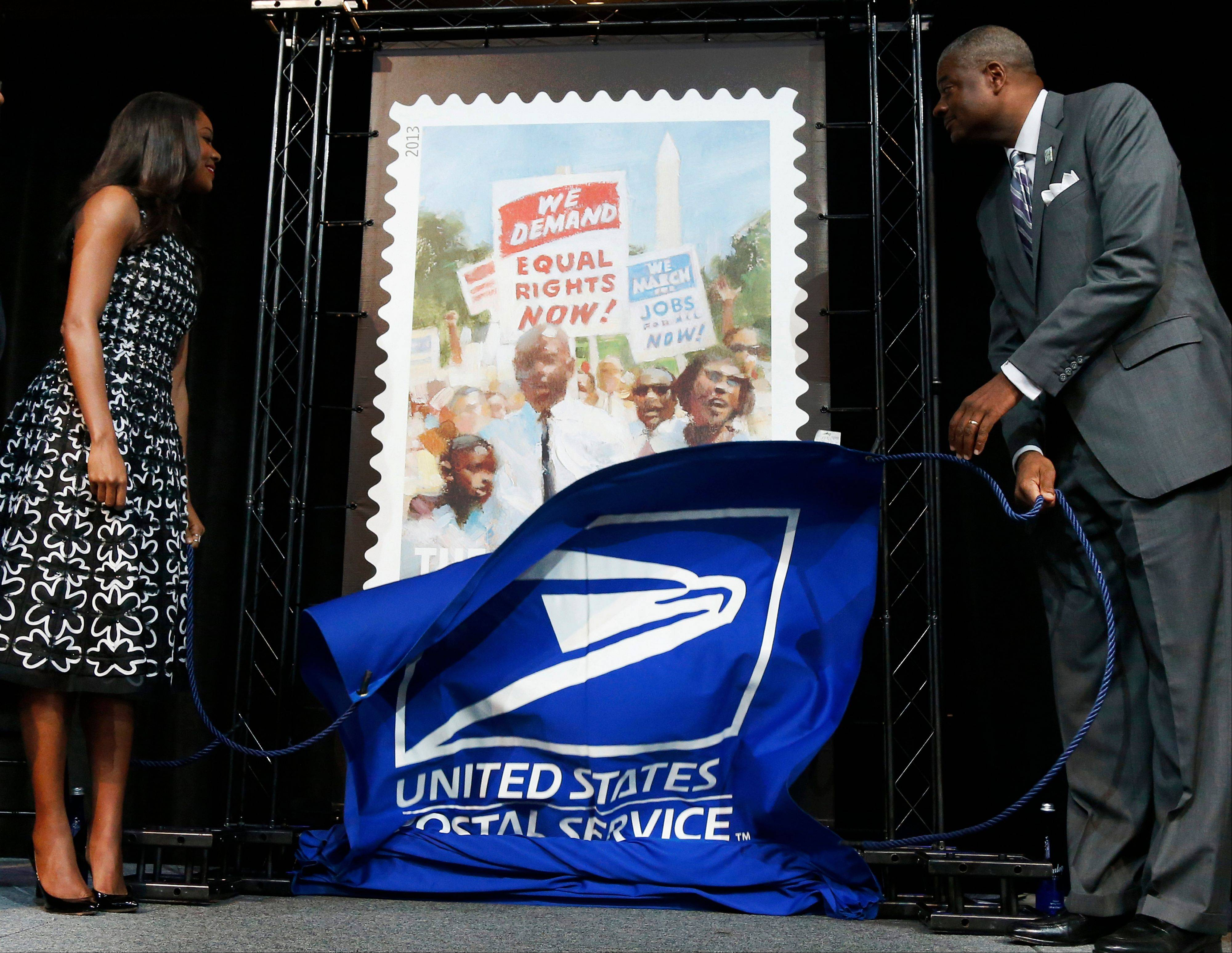 Actress Gabrielle Union and Deputy Postmaster General Roland A. Stroman unveil of a U.S. Postal Service stamp Friday commemorating the 50th anniversary of the March on Washington.