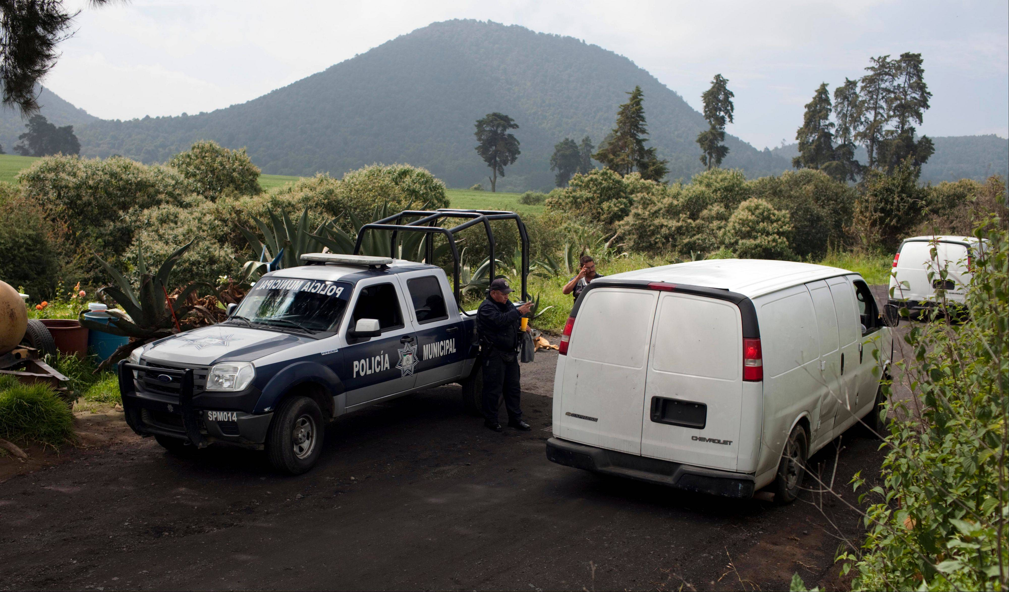 Vans belonging to Mexican authorities arrive at the entrance of a ranch where a mass grave was found in Tlalmanalco, Mexico.