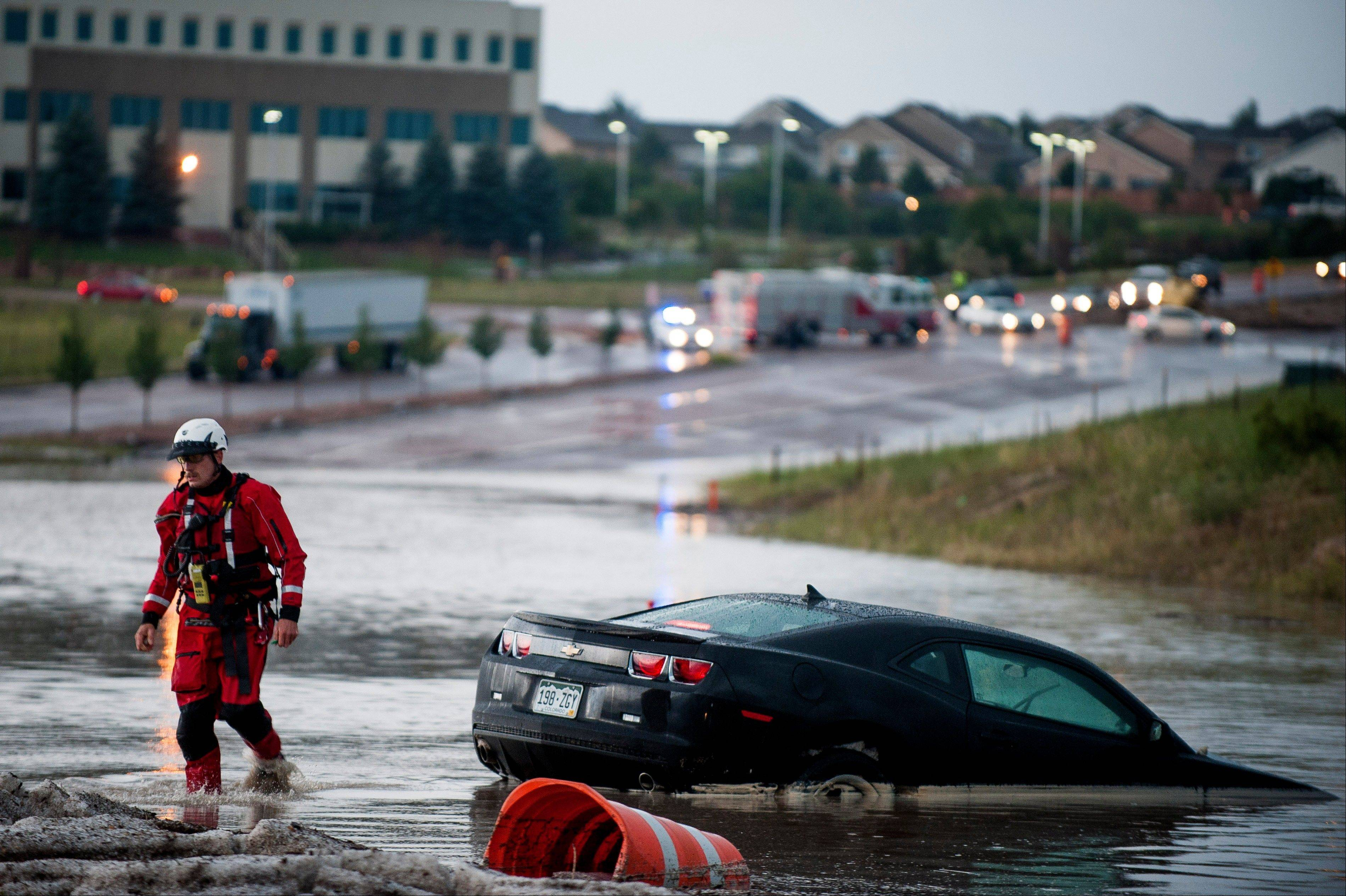 Keith Williams, with Colorado Springs Heavy Rescue, walks away from a car that was submerged when flash floodwaters rushed over Voyager Parkway near Copper Center Parkway Thursday, Aug. 22, 2013 in Colorado Springs, Colo.