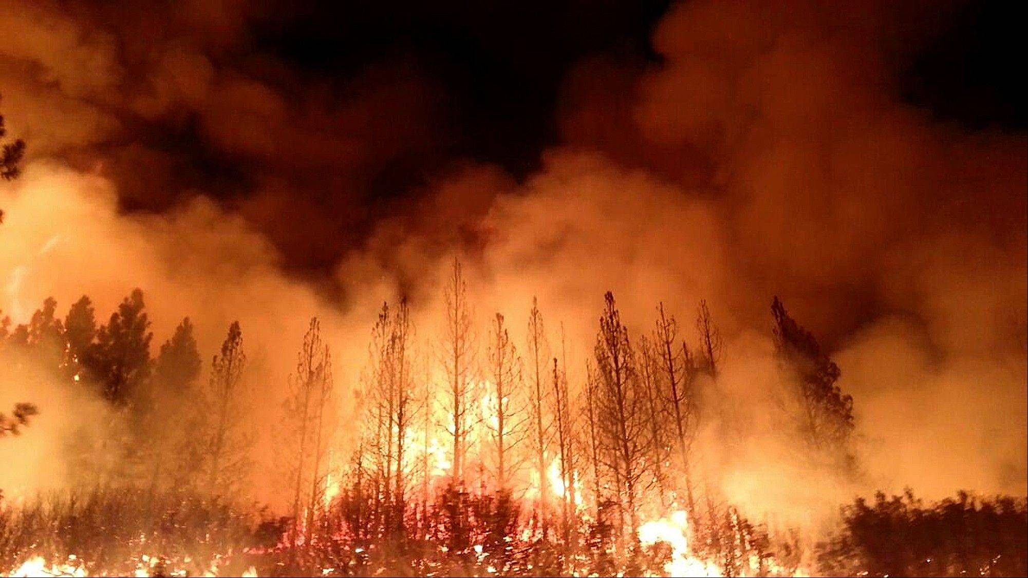The wildfire outside Yosemite National Park � one of more than 50 major brush blazes burning across the western U.S. � more than tripled in size overnight and still threatens about 2,500 homes, hotels and camp buildings.