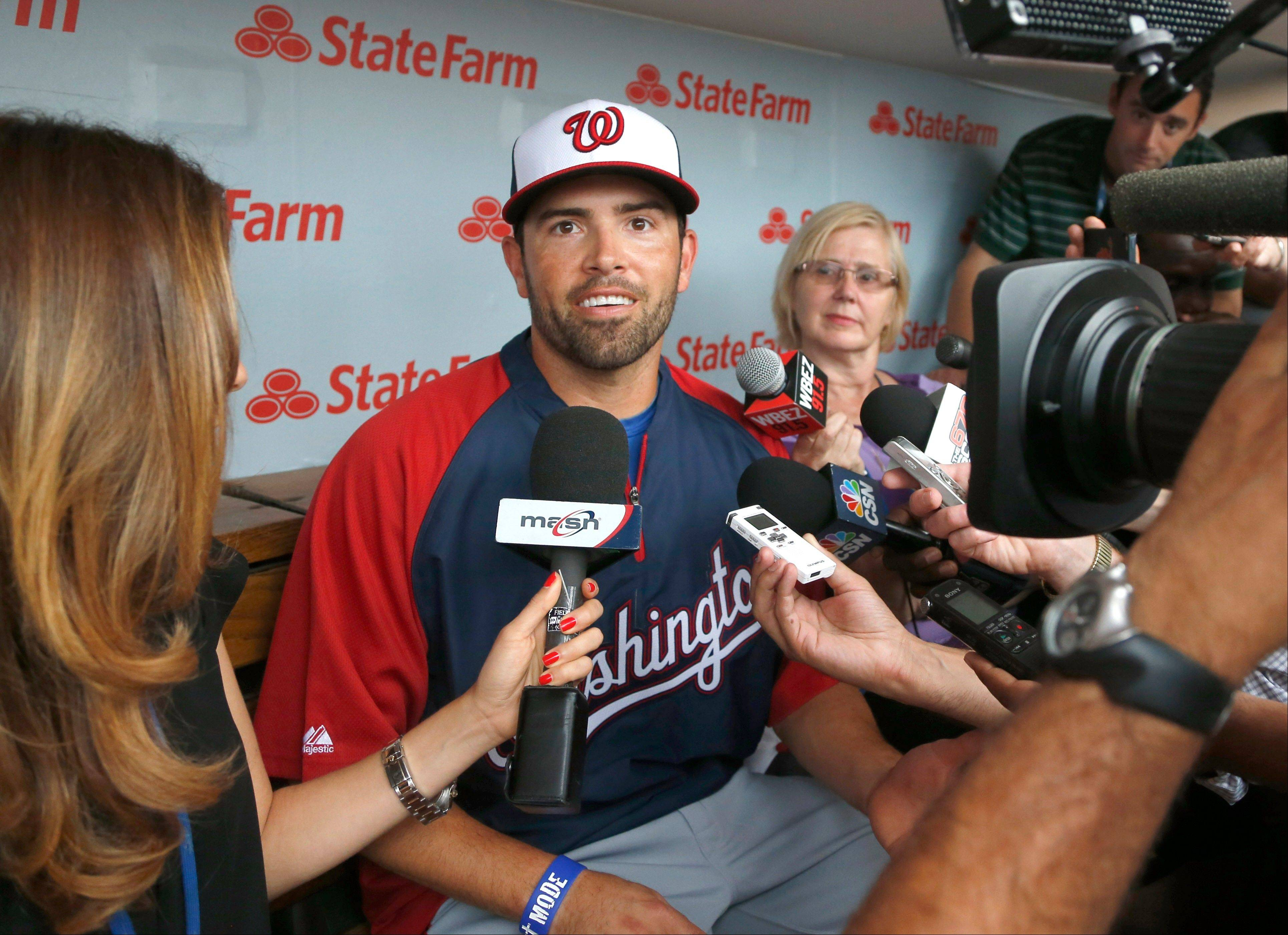 David DeJesus, center, talks with reporters Monday after he was traded by the Chicago Cubs to the Washington Nationals. Now he�s headed to the Tampa Bay Rays.