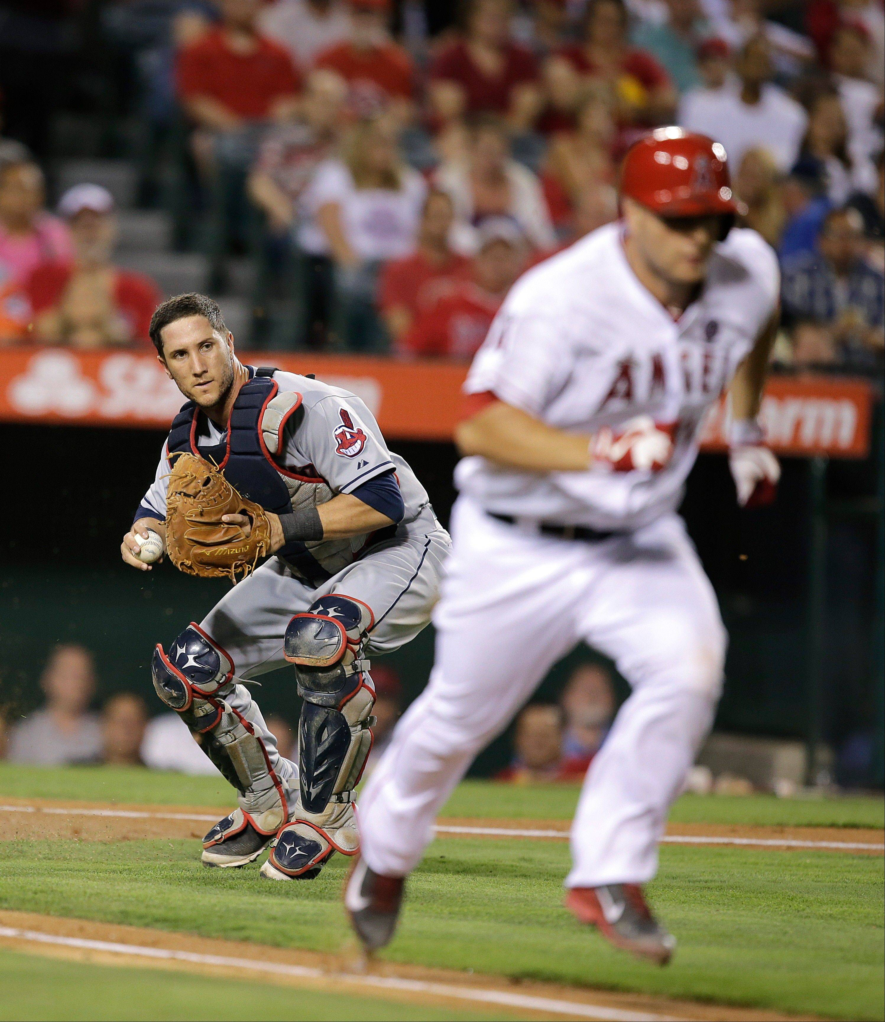 Cleveland Indians catcher Yan Gomes, left, looks to throw the ball to first base to force out Los Angeles Angels' Chris Iannetta during the fourth inning of a baseball game on Tuesday, Aug. 20, 2013, in Anaheim, Calif. (AP Photo/Jae C. Hong)