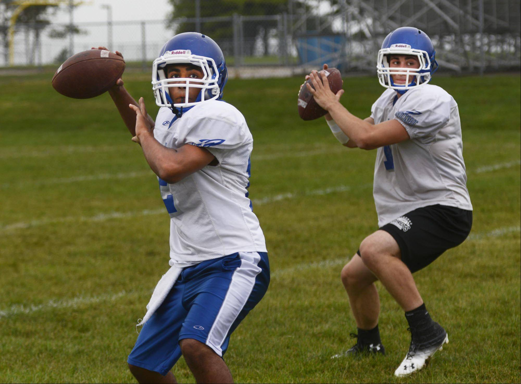 Quarterbacks Parth Patel, left, and Casey Matthews drop back during drills at Burlington Central.
