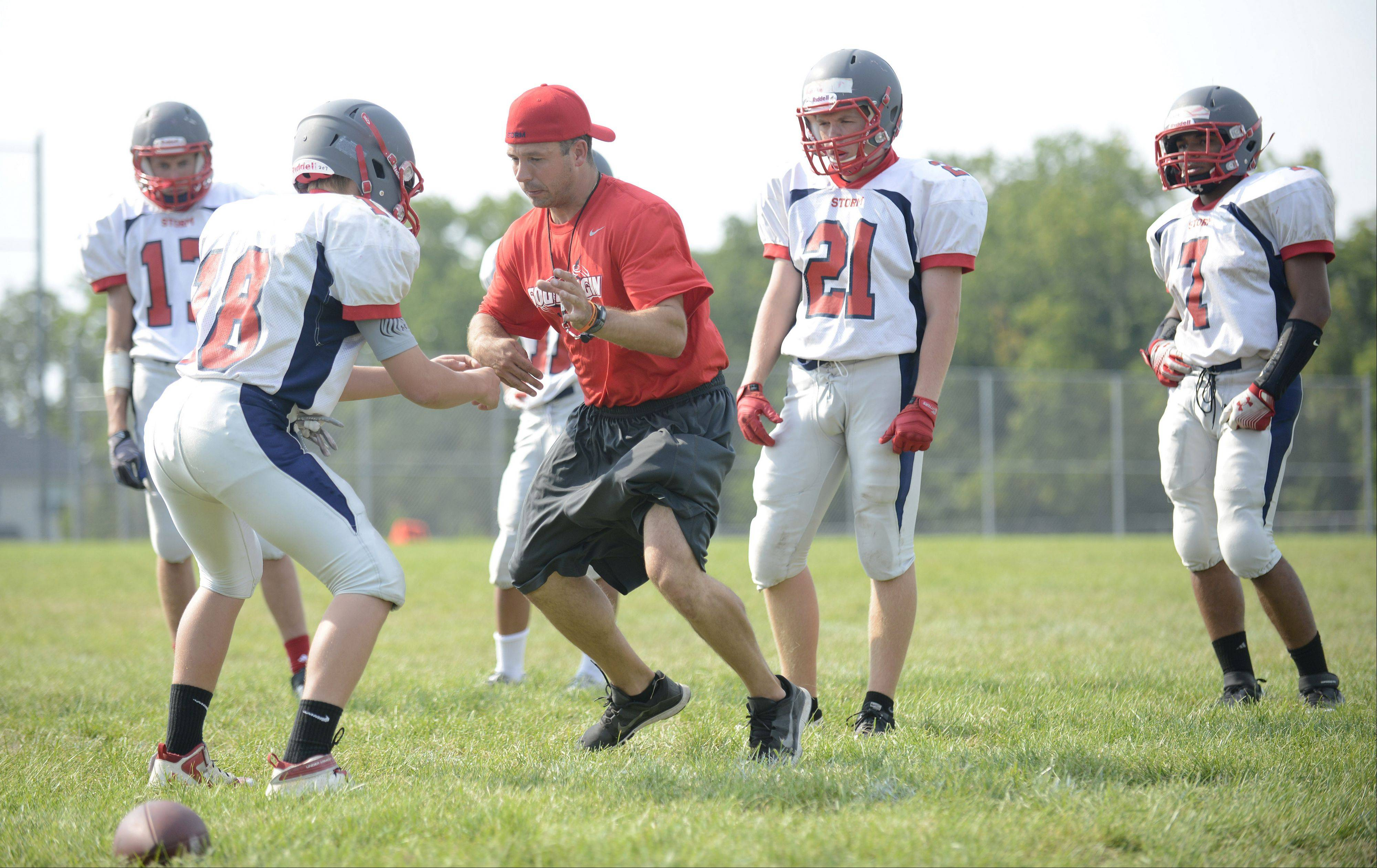 New South Elgin varsity football coach Pat Pistorio shows players how to break away from an opponent�s grip during practice.