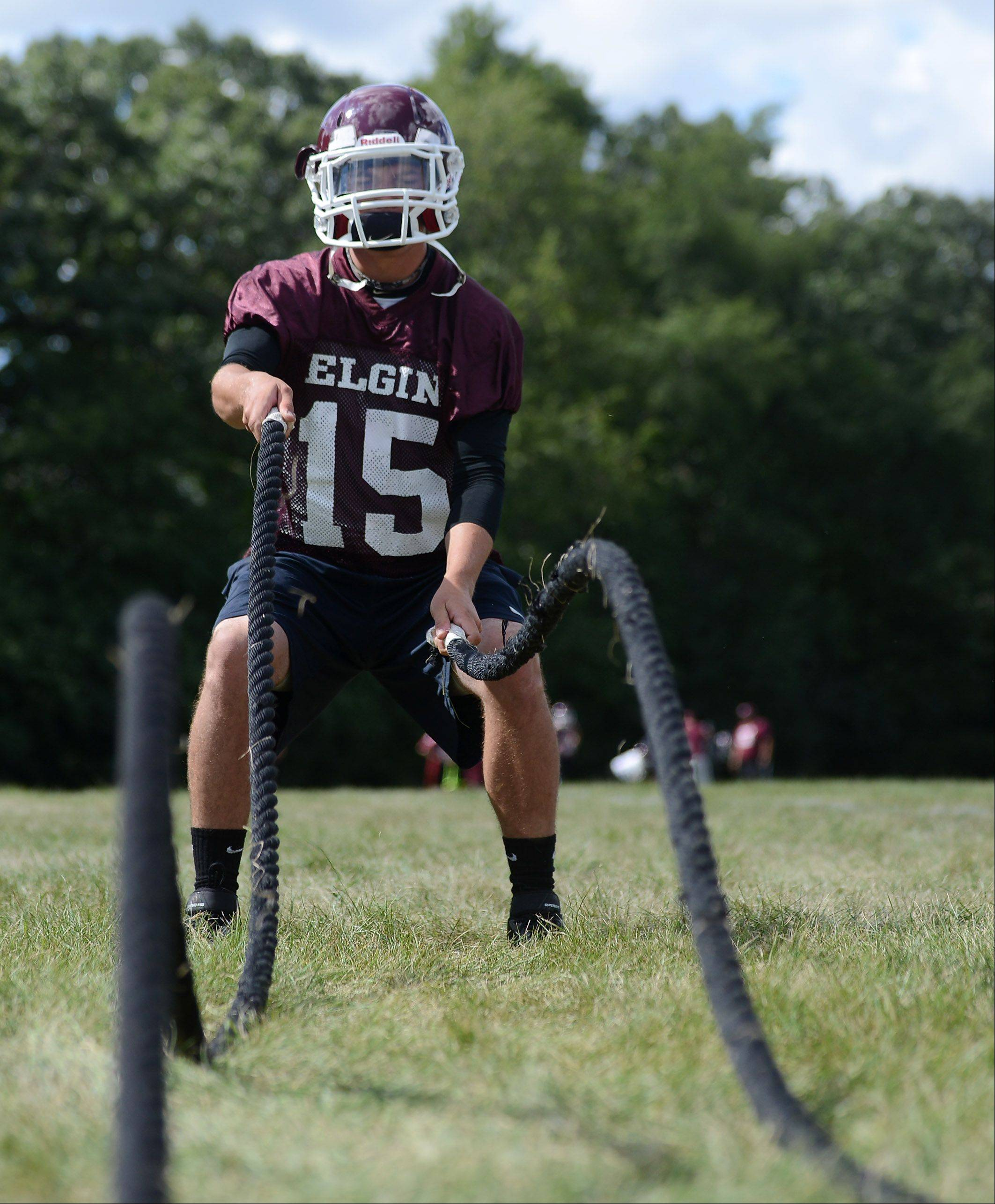 Senior quarterback Ryan Sitter works out during the first day of fall football practice at Elgin High School.