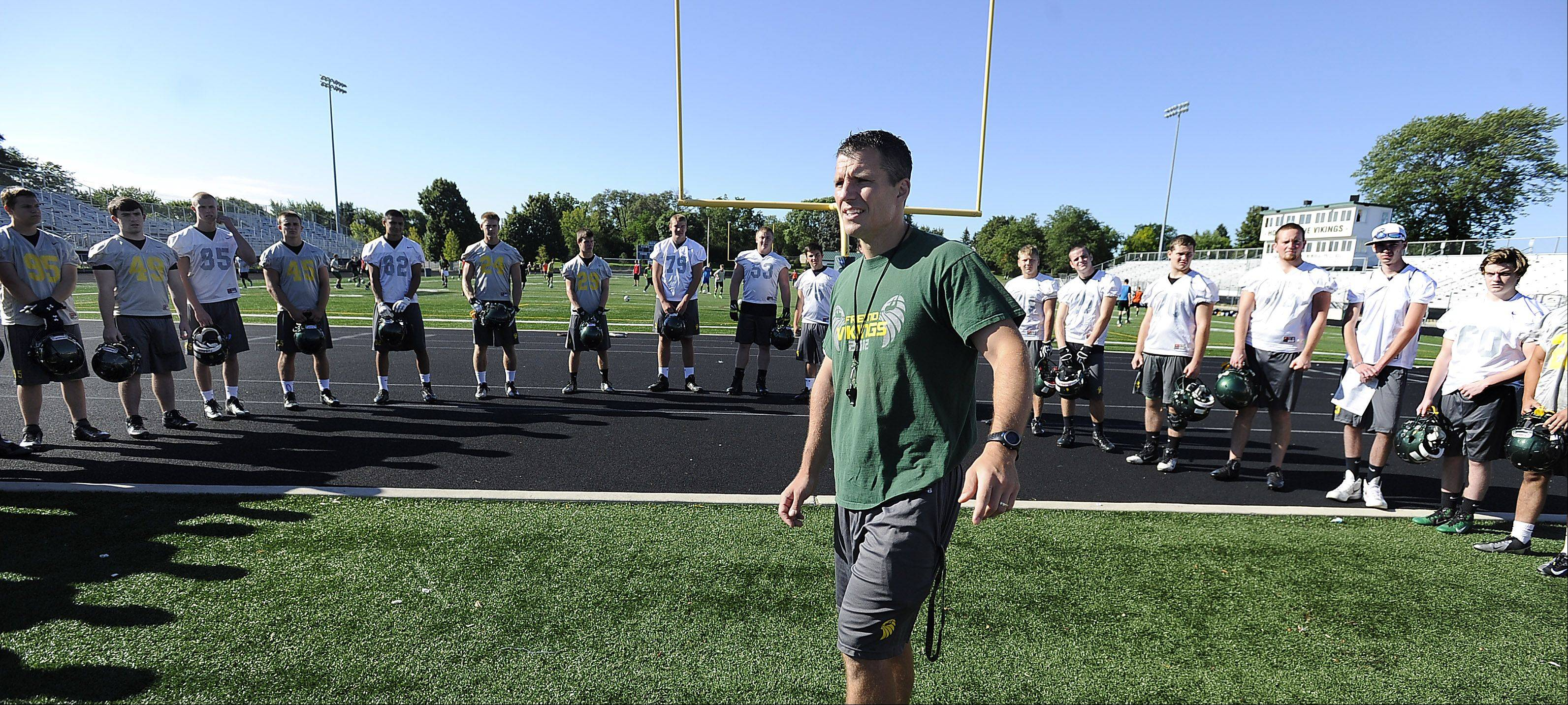 Coach Lou Sponsel works with his players at Fremd on the first day of official practice for the 2013 season.