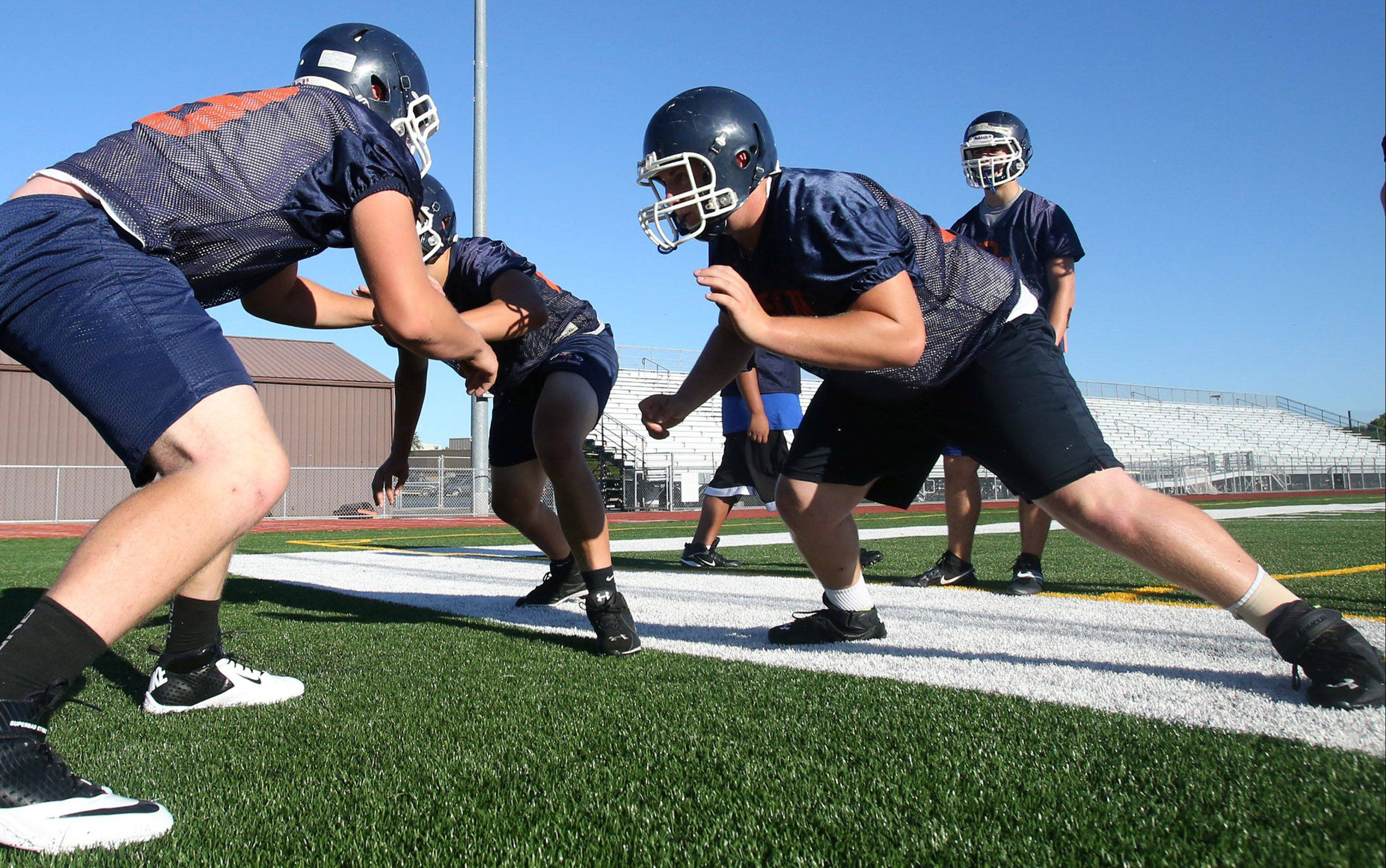 Tackle Aaron Schubert, right, works in drills against defensive players on the first day of practice for the 2013 season.