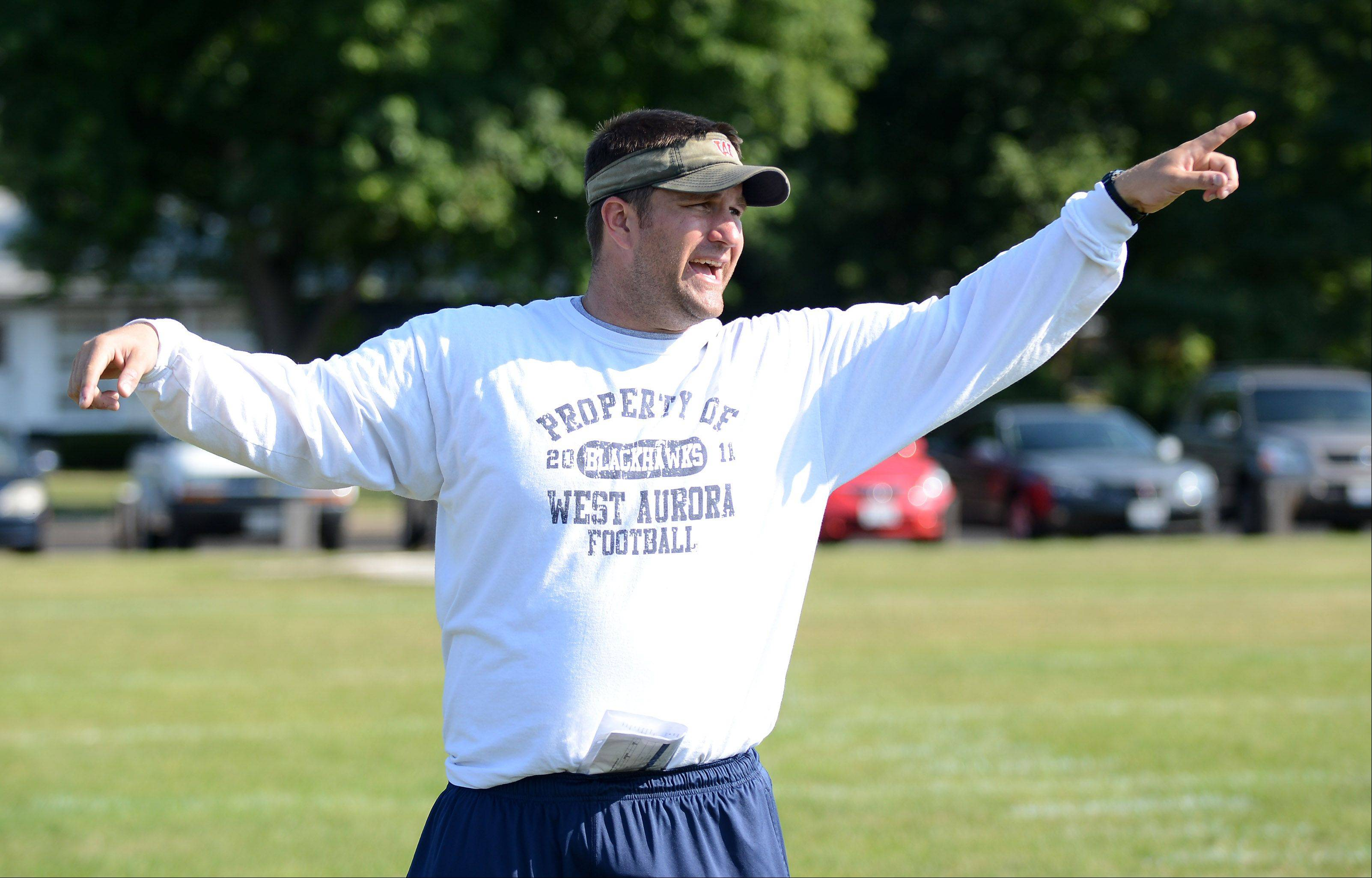 Coach Nate Eimer leads his team during West Aurora football practice Friday.