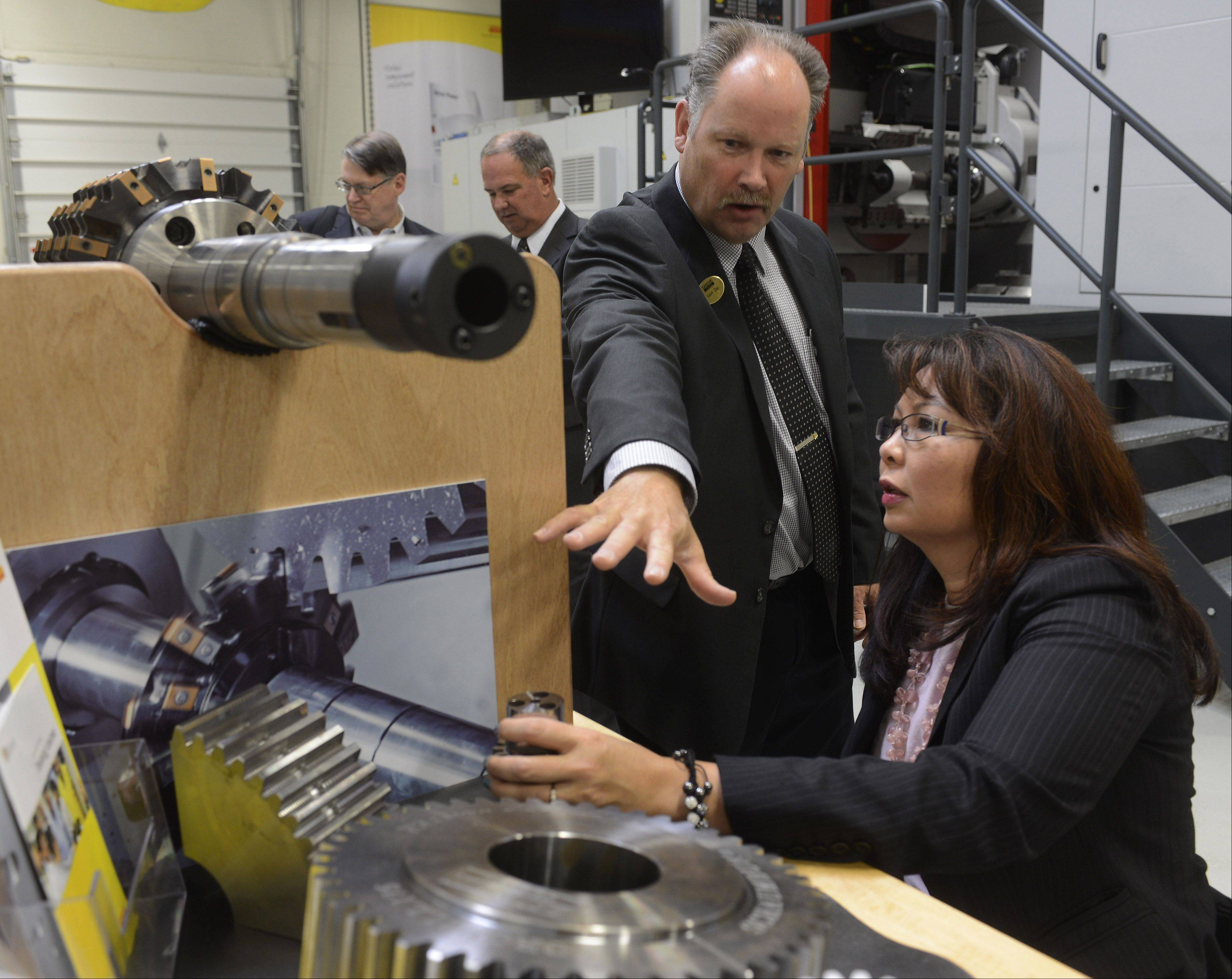 Kevin Clay, productivity center and training manager of Sandvik Coromant Co. in Schaumburg, shows a gear-cutting tool and a gear to U.S. Rep. Tammy Duckworth, a Hoffman Estates Democrat, following a discussion on manufacturing and its importance to the suburban region.