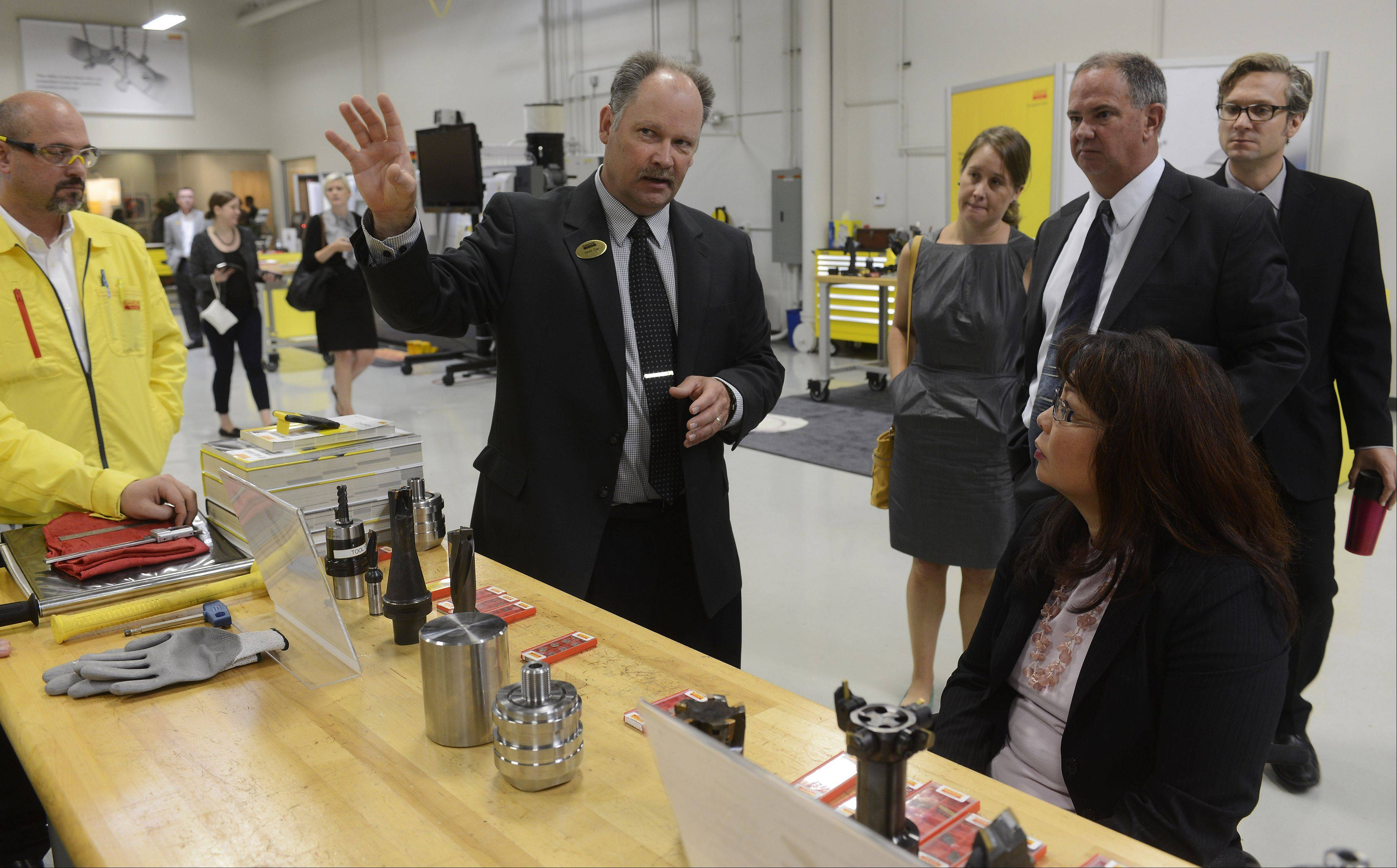 Kevin Clay, productivity center and training manager of Sandvik Coromant Co., Schaumburg, leads a tour which includes U.S. Rep. Tammy Duckworth, a Hoffman Estates Democrat, right, at the company's facility Friday. The company hosted a discussion on manufacturing and its importance to the region.
