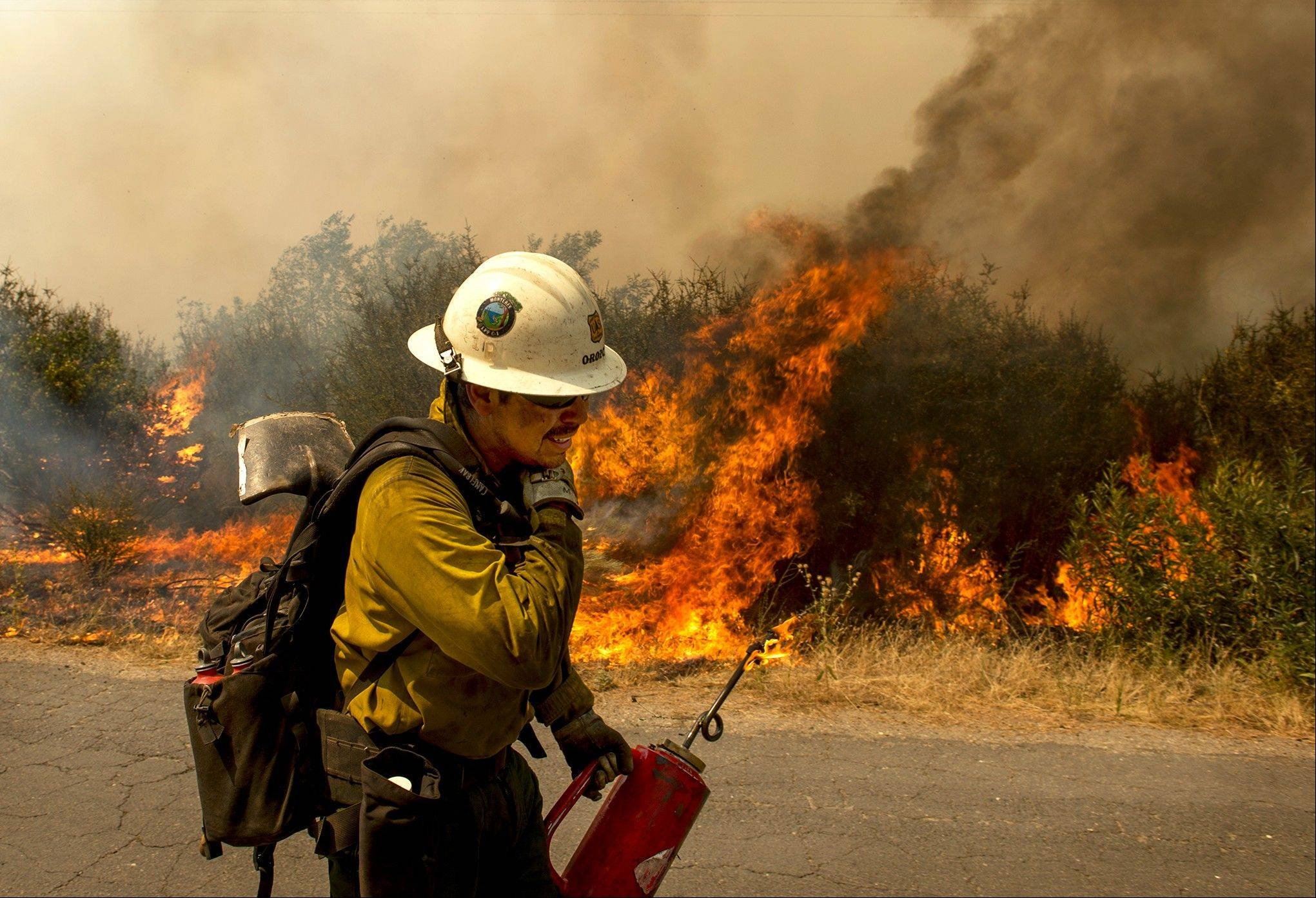 A U.S. Forest Service firefighter moves away from a quickly moving section of the Rim Fire in the Stanislaus National Forest Tuesday, Aug. 20, 2013.