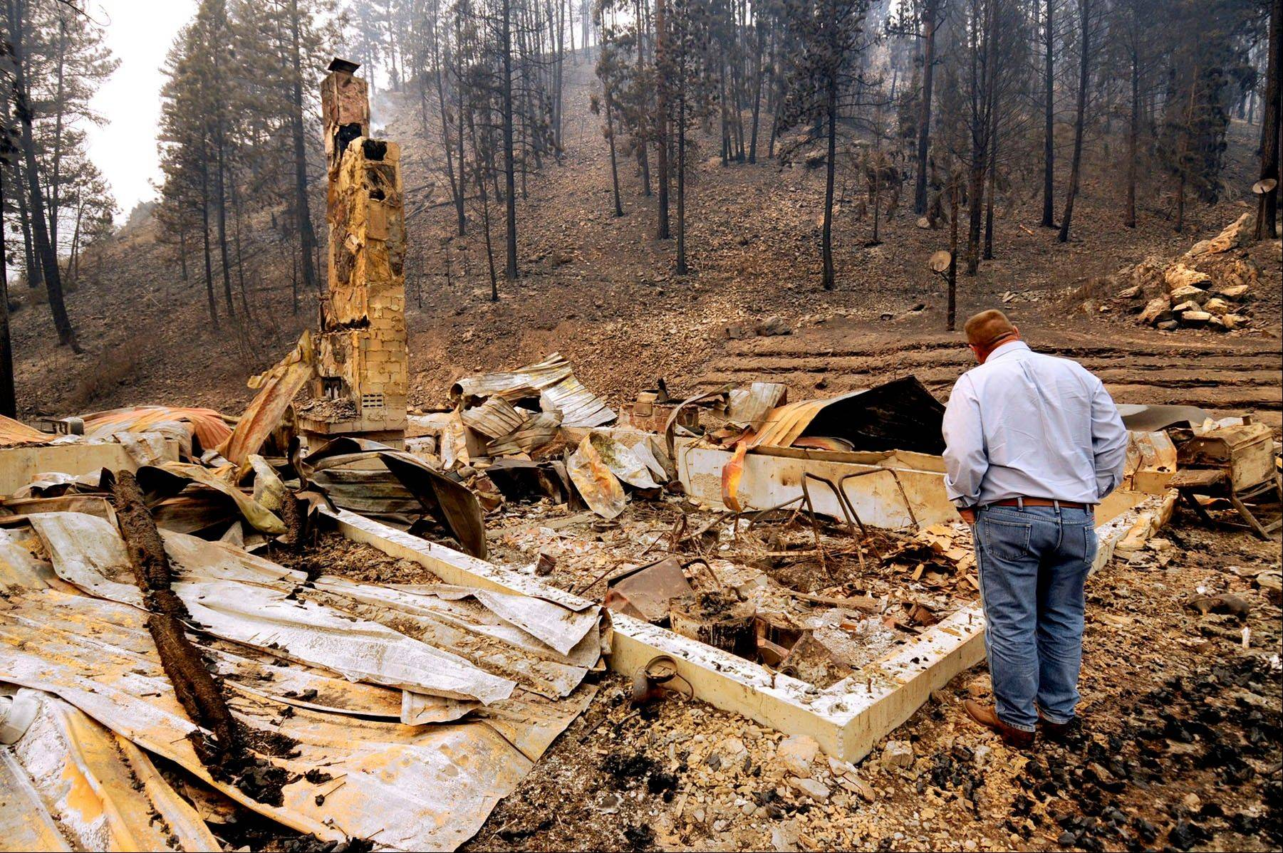 U.S. Sen. Jon Tester, D-Mont., looks at the remains of a Lolo Creek home that was destroyed by the West Fork II fire when it swept down the Lolo Creek canyon, Wednesday, Aug. 21, 2013 near Lolo, Mont. The fire burned four other homes as well along the U.S. Highway 12 corridor.
