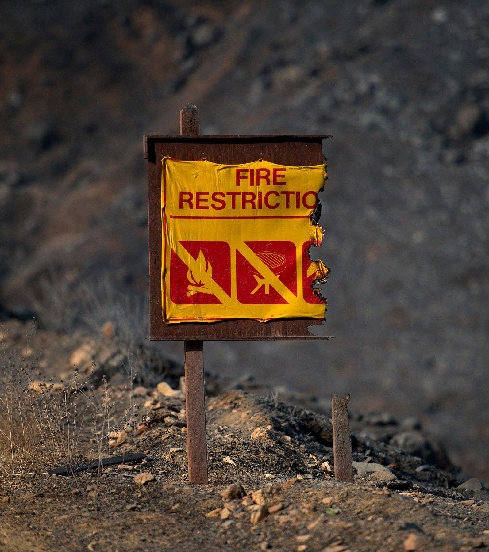 A fire restrictions sign is partially burned away by the Rim Fire in the Stanislaus National Forest Thursday, Aug. 22, 2013, in California. California Gov. Jerry Brown declared a state of emergency due to the huge fire, one of several blazes burning in or near the nation's national parks and one of 50 major uncontained fires burning across the western U.S.