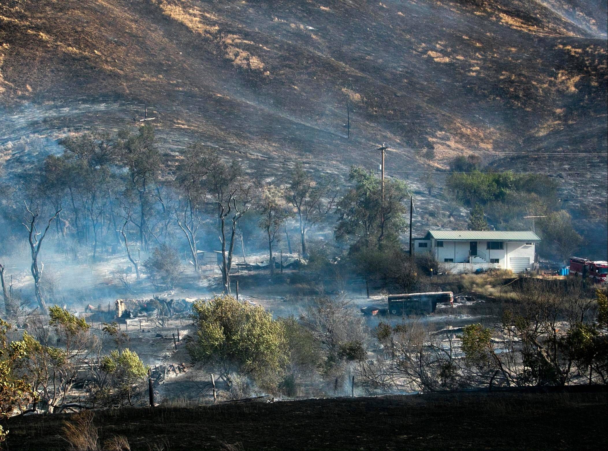 Firefighters battle a wildfire near mile marker 14 on Idaho 21 near Hilltop Cafe northeast of Boise Tuesday Aug. 20, 2013. The blaze was reported to have destroyed two structures. Firefighting efforts saved a home that was clearly surrounded by charred ground.