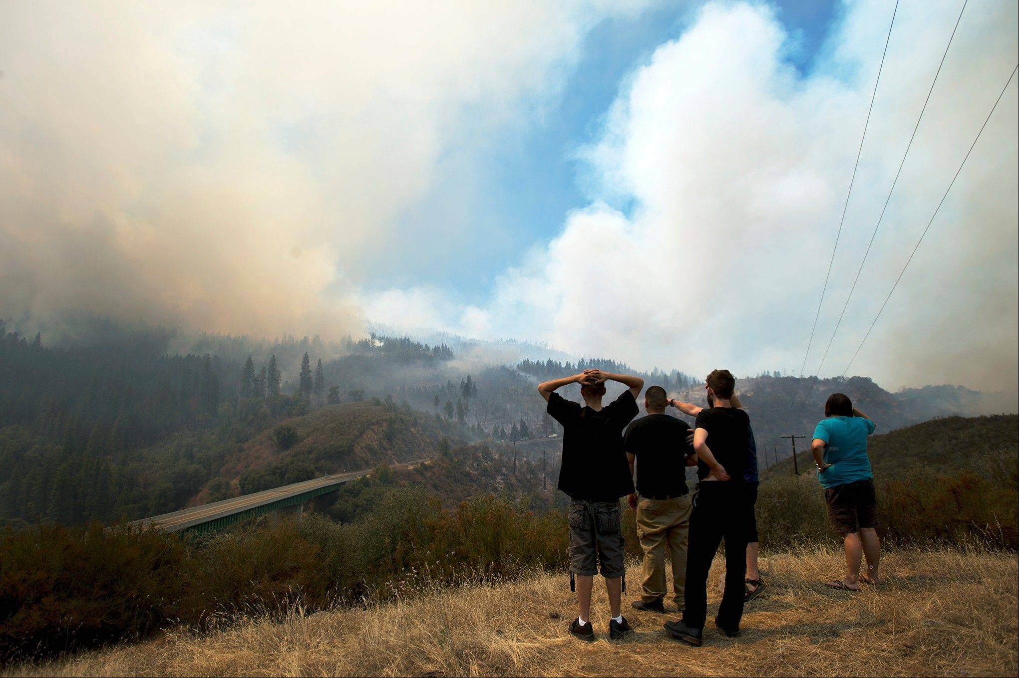 Friends Mike Geiser, Rene Auitia, Marcos Lopez, Ashton Humphrey and Nick Ward look out over the Tuolumne River Canyon as the Rim Fire moves east along Highway 120 in the Stanislaus National Forest Tuesday Aug. 20, 2013.