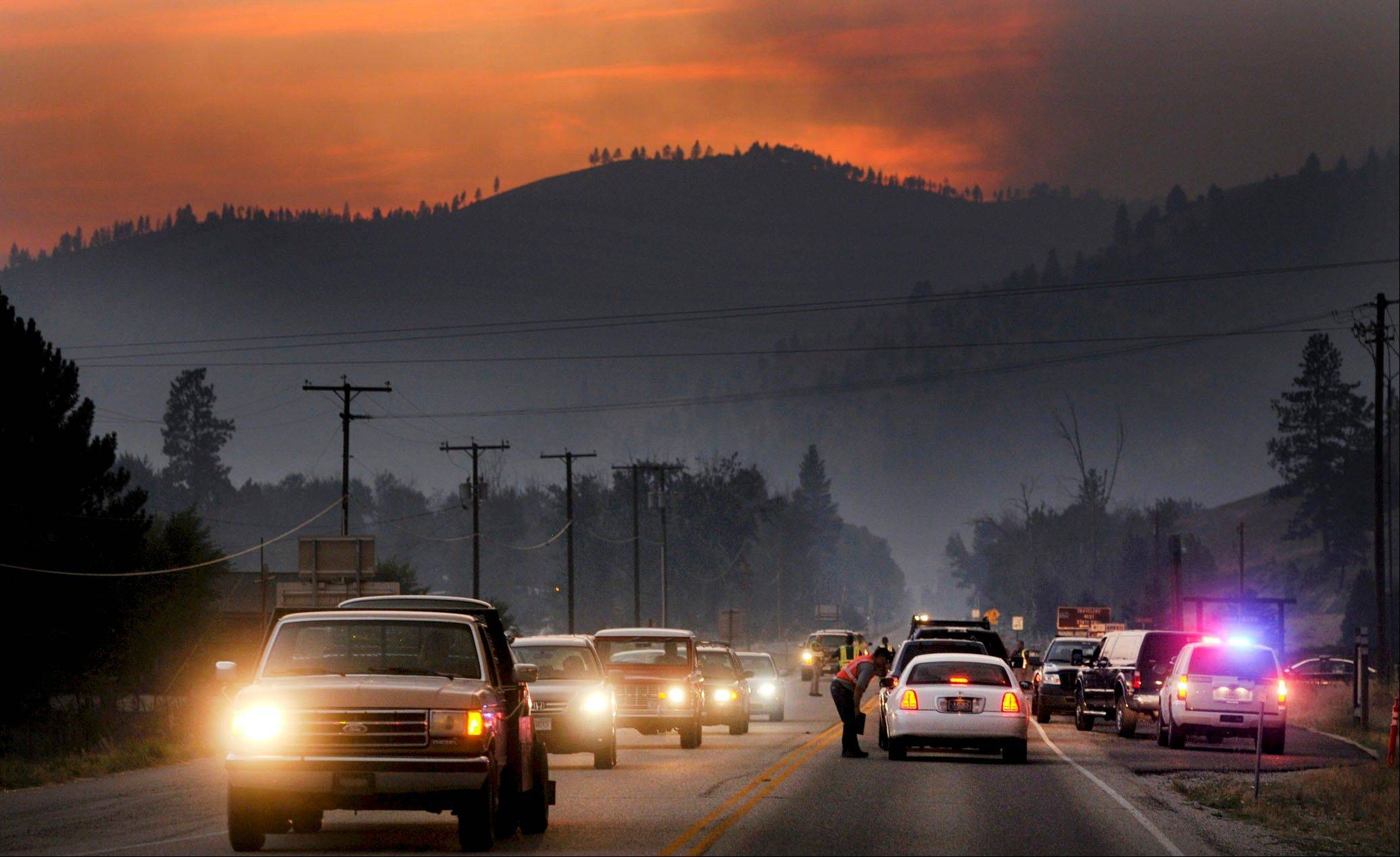 A line of evacuees, forced from the Lolo Creek drainage near Lolo, Mont., by the Lolo Creek Complex of fires, passes through a roadblock Tuesday evening, August 20, 2013, at the intersection of U.S. Highway 12 and U.S. Highway 93 South. The fire complex grew to 8,000 acres Tuesday evening forcing more evacuations.
