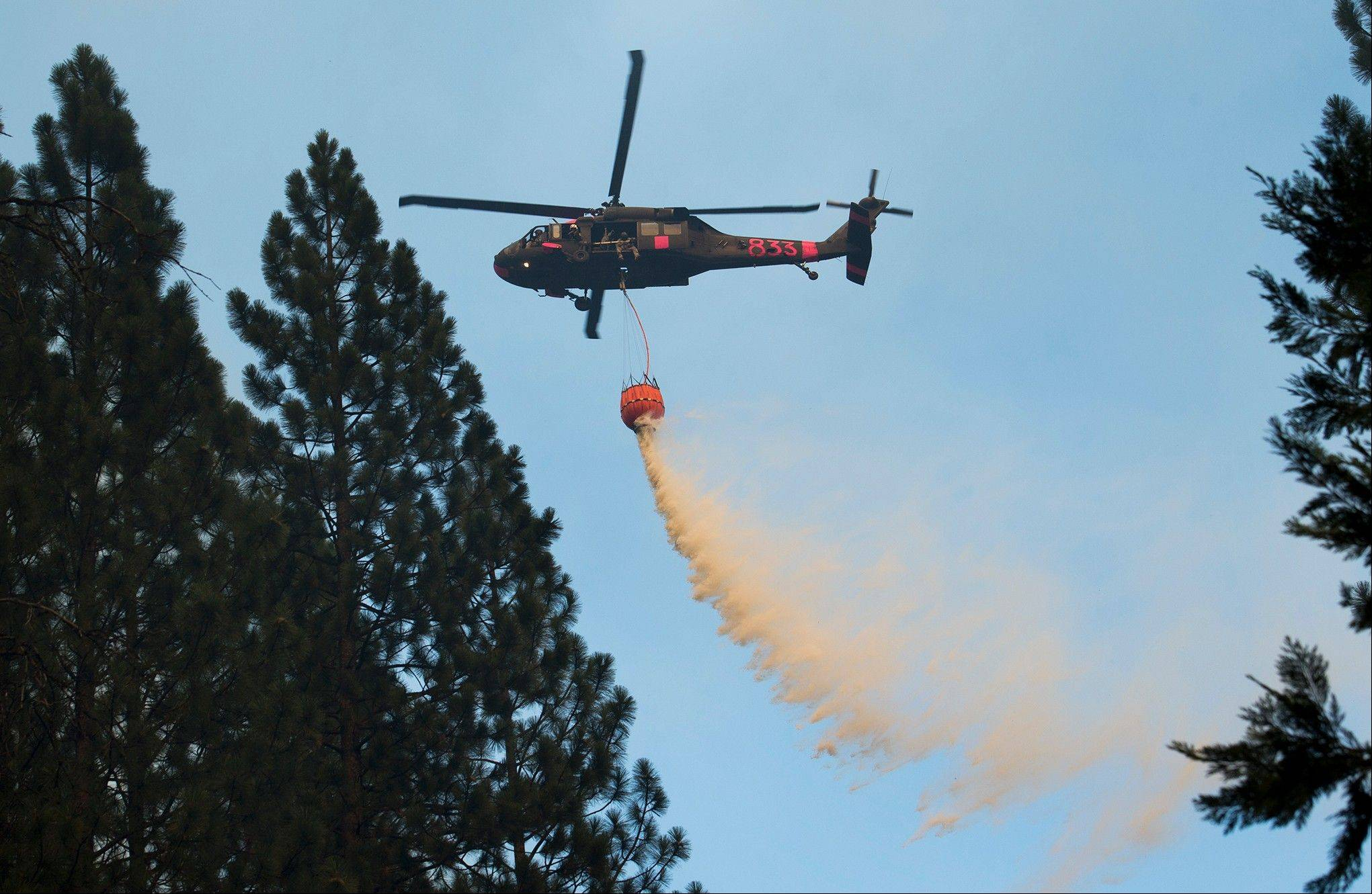 A helicopter makes an aerial water drop over the Rim Fire in the Stanislaus National Forest Thursday, Aug. 22, 2013. A wildfire outside Yosemite National Park nearly quadrupled in size Thursday, prompting officers to warn residents in a gated community to evacuate their homes and leading scores of tourists to leave the area during peak season.