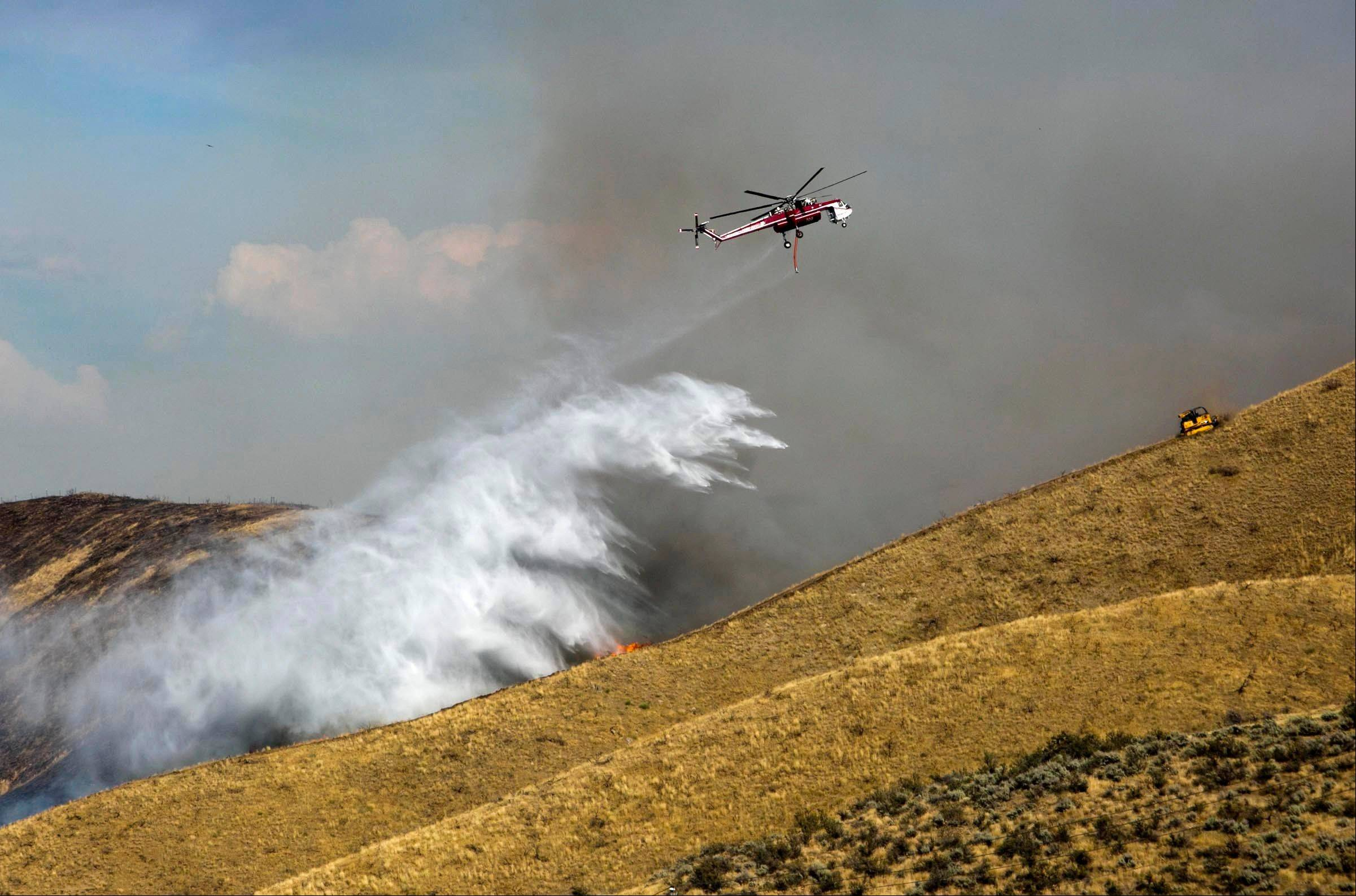A fire attack helicopter drops water along a draw northeast of Hilltop Cafe on Idaho 21 as a bulldozer plows a fire line on the ridge Tuesday Aug. 20, 2013 northeast of Boise. The National Interagency Fire Center in Boise raised the wildfire preparedness level Tuesday to the highest level for the first time in five years and listed two central Idaho wildfires as the country's top priorities.