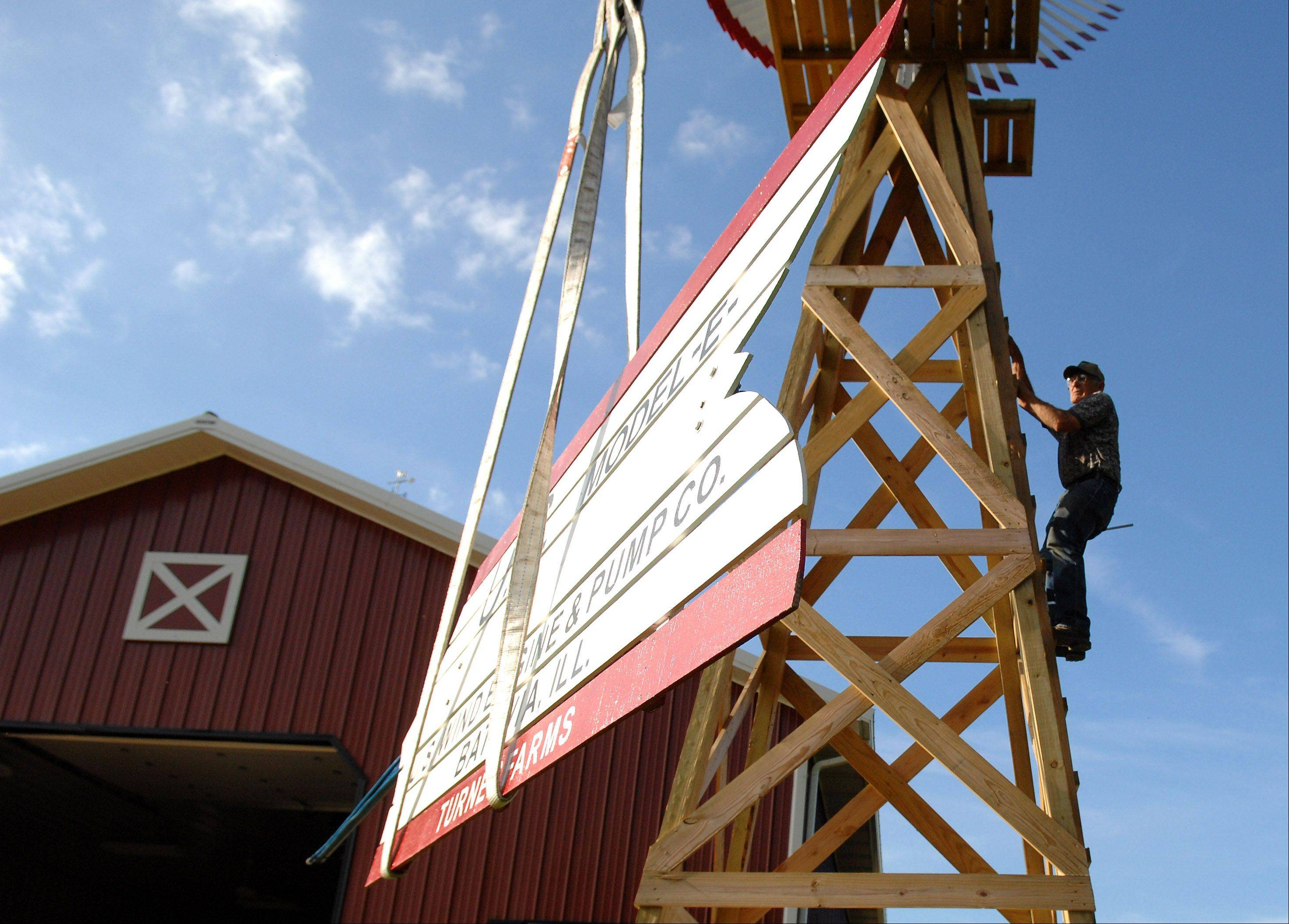 Engel climbs the tower to meet the tail as a crane lifts it to the top.