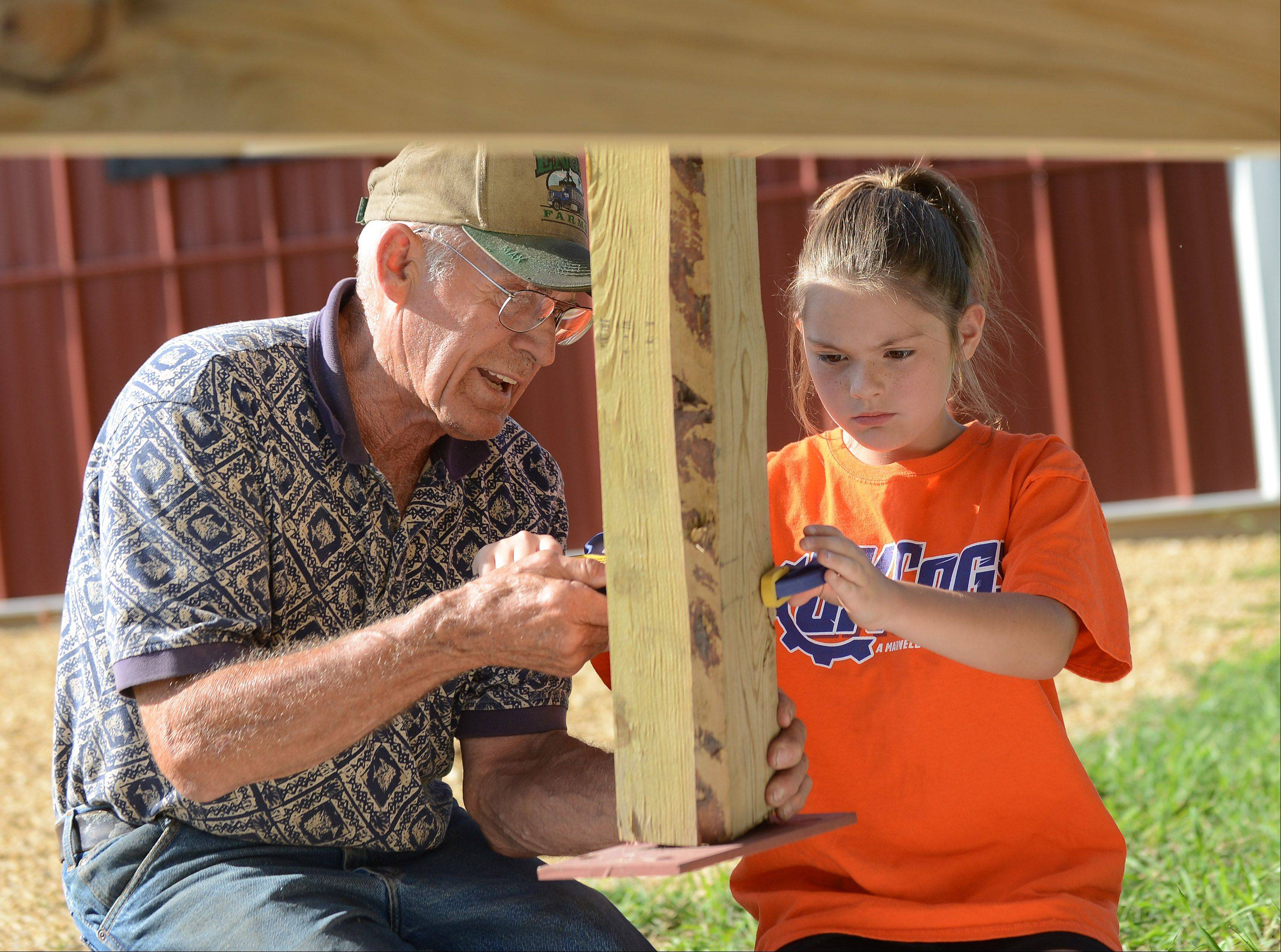 Engel gets a hand from his granddaughter Mackenzie, 9, while installing a tower in Garden Prairie.