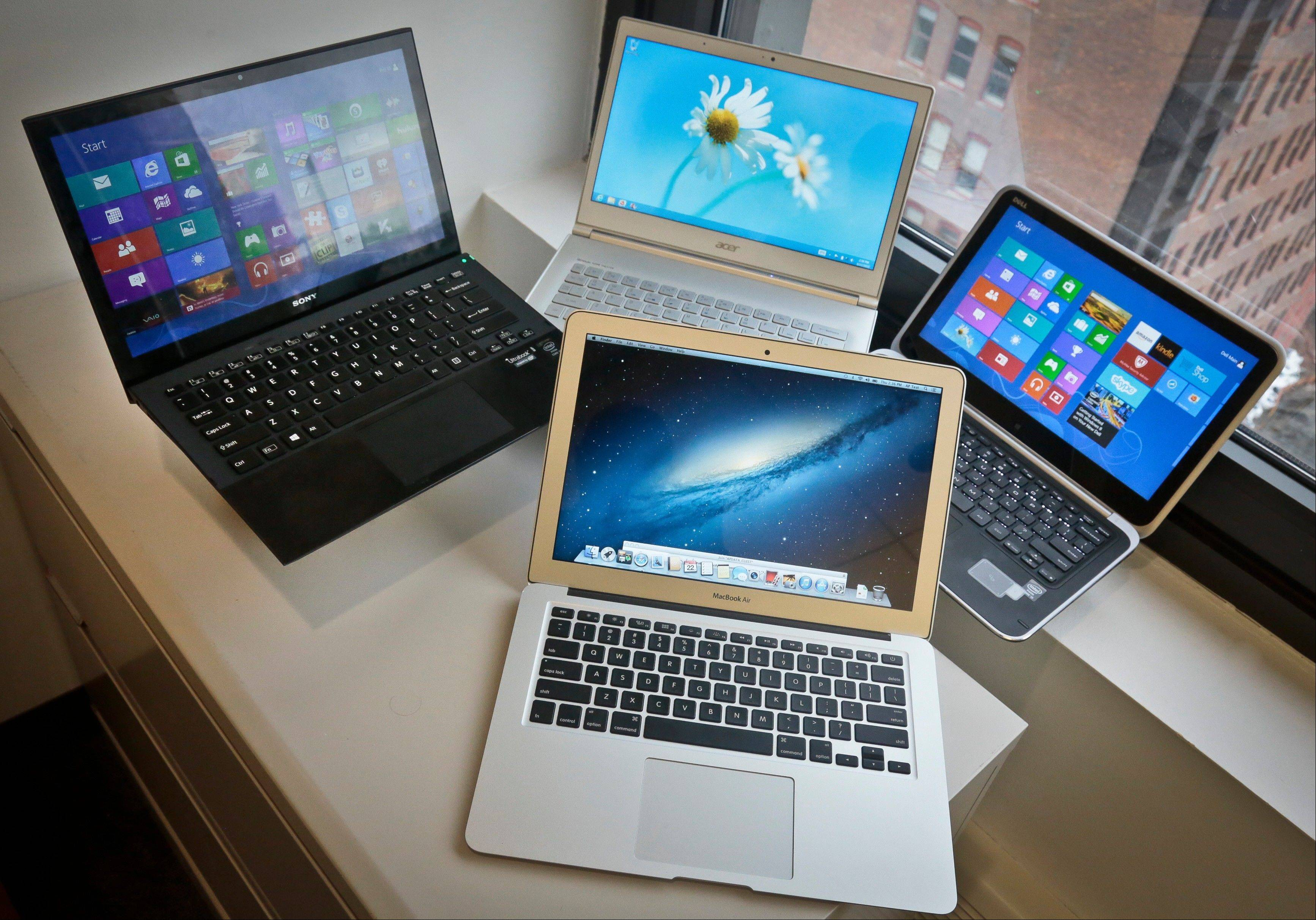 A MacBook Air from Apple, bottom center, a Vaio Pro 13 from Sony, top left, an Aspire S7 from Acer, center, and an XPS 12 from Dell, right, are displayed. Each notebooks has a microprocessors that belongs to a new family of Intel chips called Haswell.