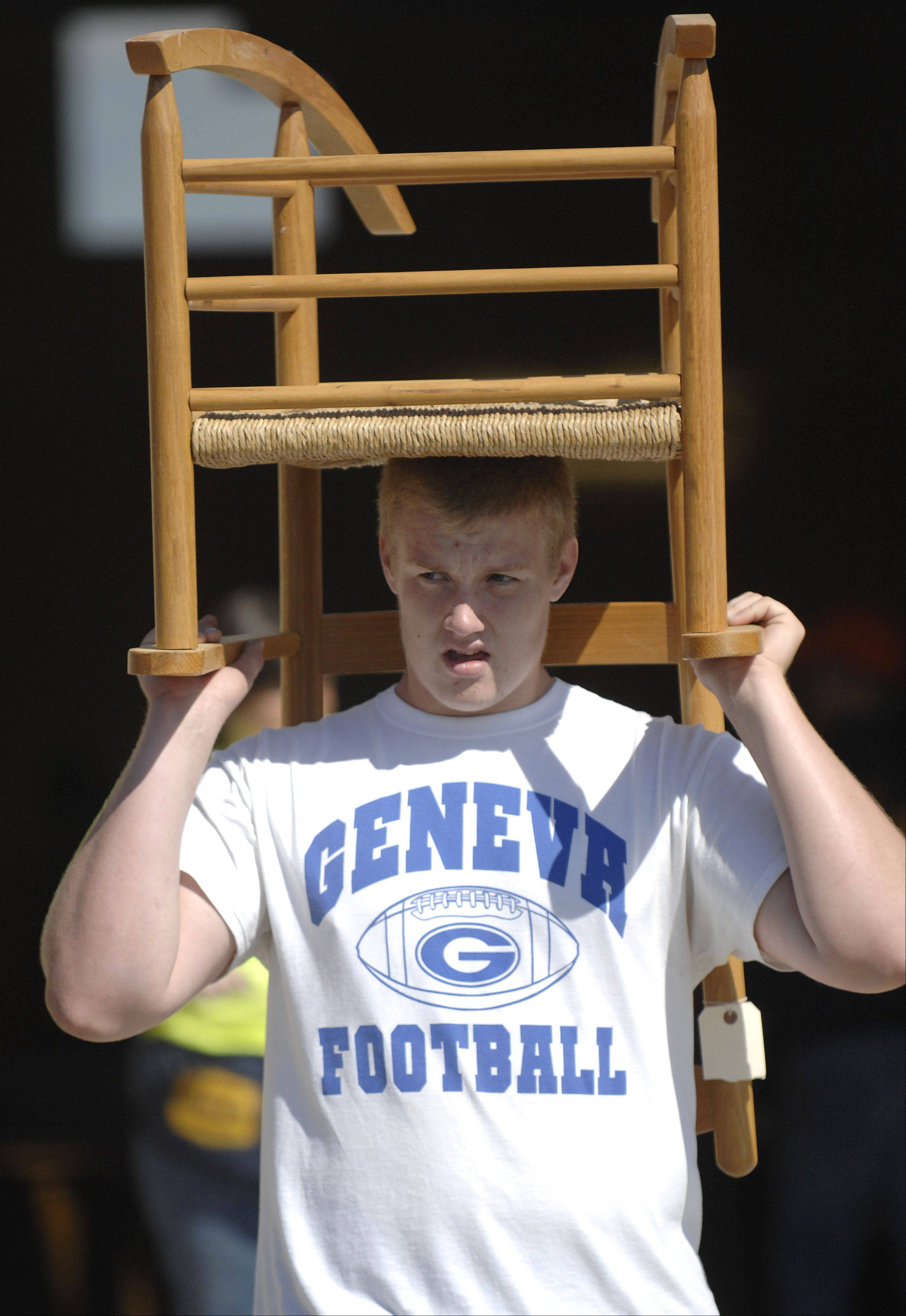 Volunteer Jacob Bastin, 16, of Geneva, moves a purchased chair to the pickup lot at the Kane County Fairgrounds during the St. Peter Barn Sale in September 2011. This year�s barn sale is Sept. 14 and 15 at the fairgrounds.
