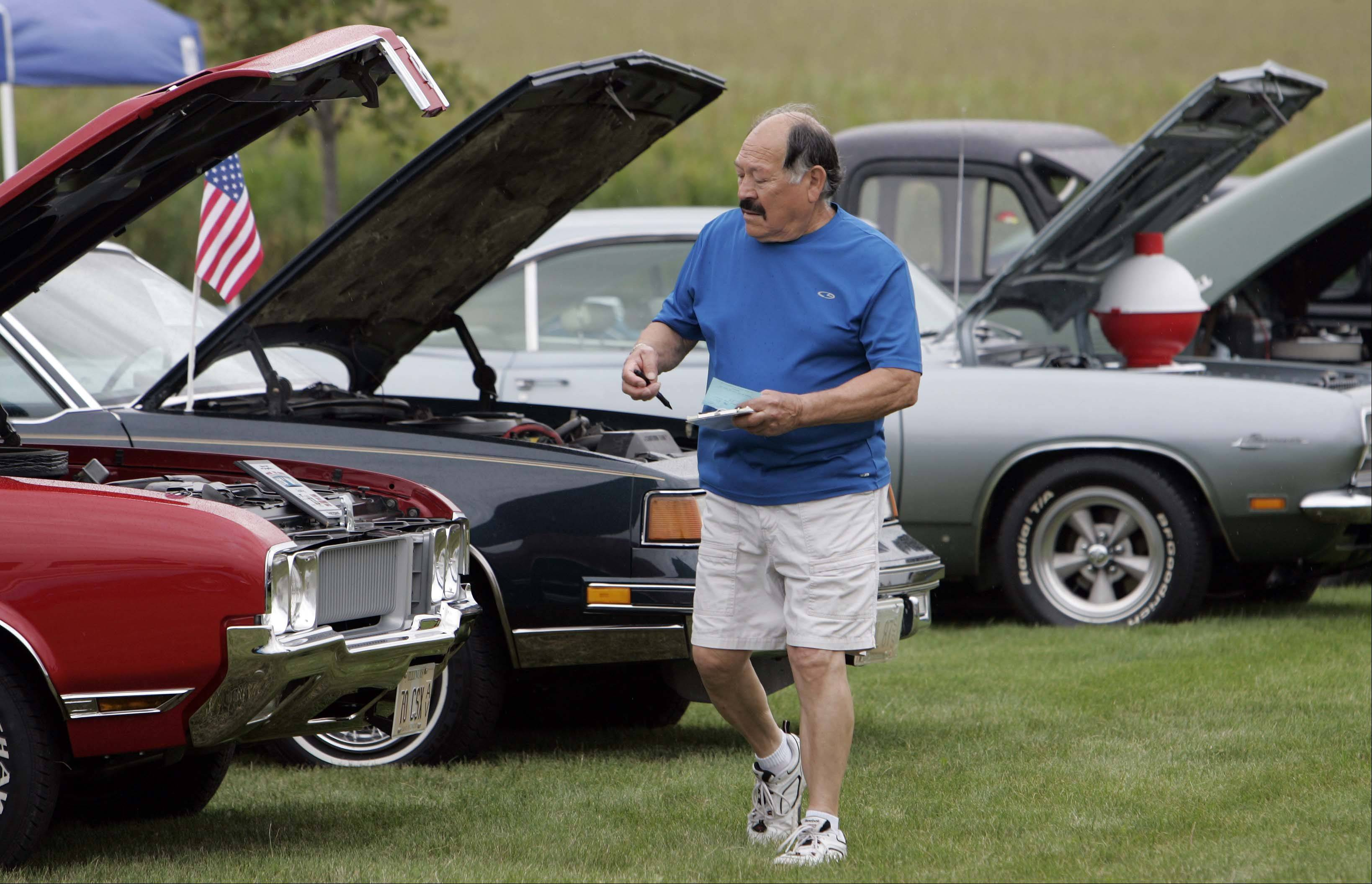 Lee Gomez of St. Charles gets a look at some of the cars during Kane County Sheriff Pat Perez�s sixth annual charity car and motorcycle show last year in Elburn. Gomez was showing his own six-cylinder 1965 Chevrolet Impala.