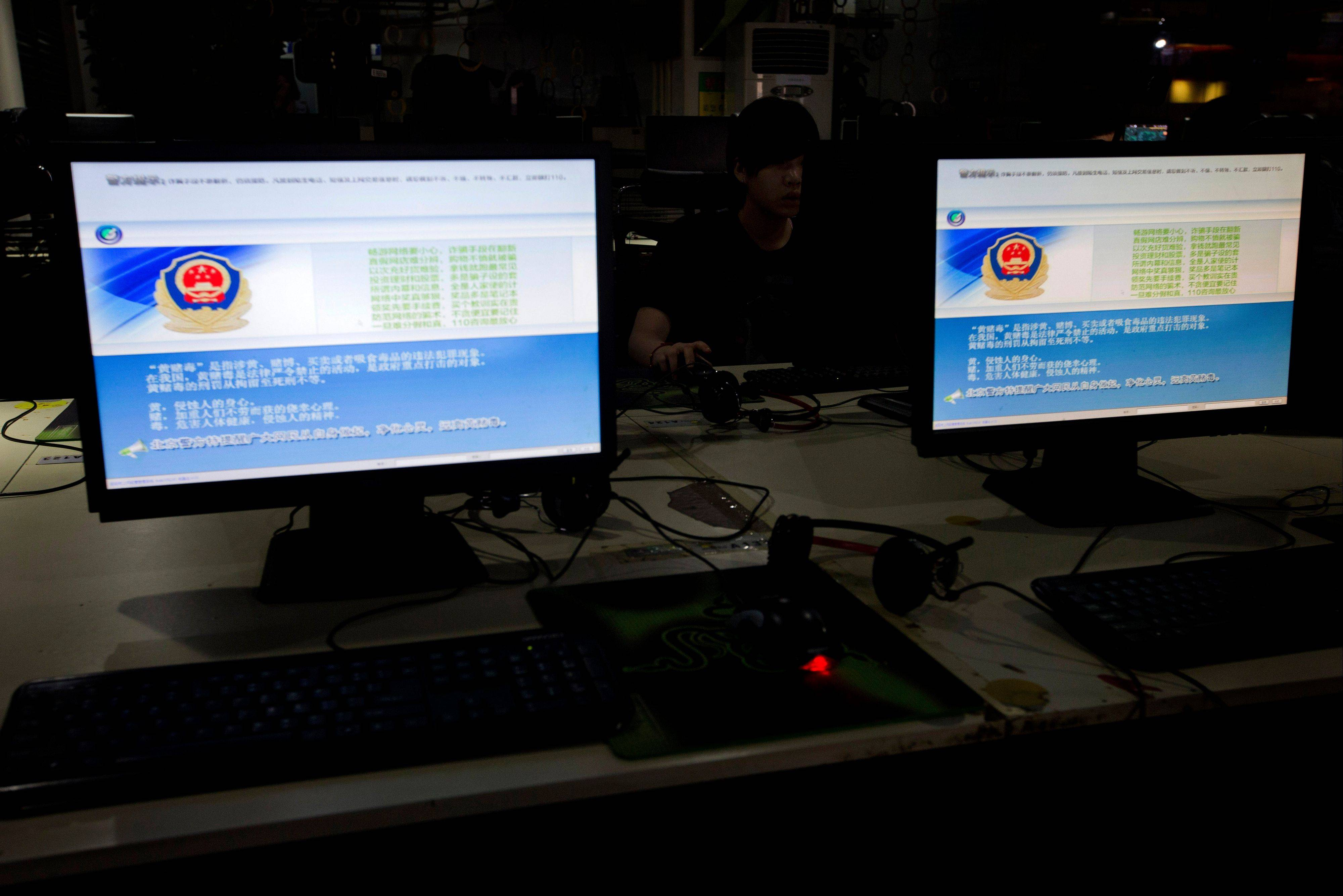 A computer user sits near displays with a message from the Chinese police on the proper use of the Internet at an Internet cafe in Beijing. Many famous Chinese -- from pop stars to scholars, journalists to business tycoons -- have amassed substantial online followings, and these larger-than-life personal