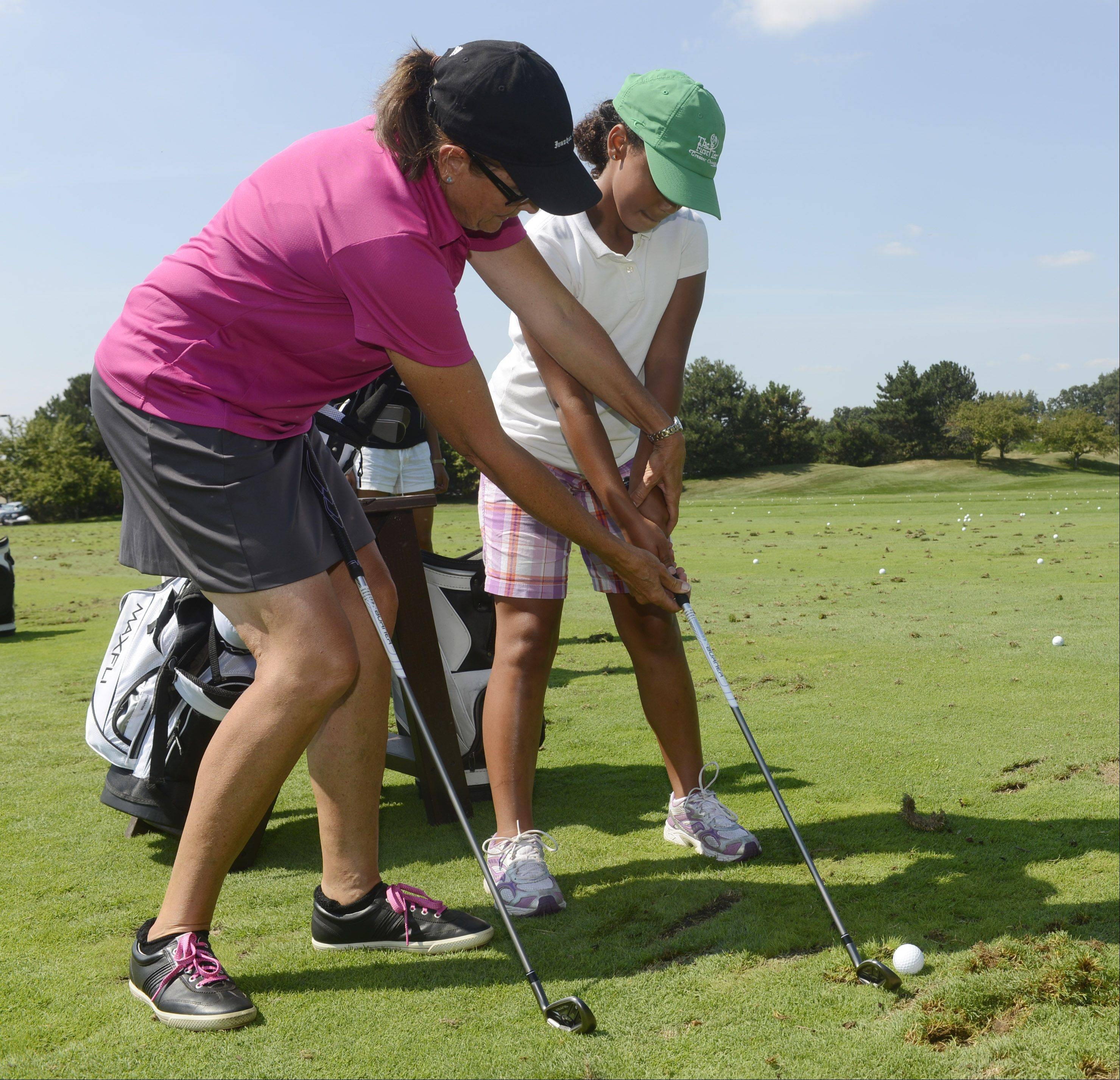 Golf pro Sue Anderson helps Zinzi Steele, 10, of Evanston during the First Tee golf event at Ivanhoe Club near Mundelein. First Tee uses the game of golf to provide education programs that build character. Thirteen kids were rewarded for their good choices with a special day at Ivanhoe.