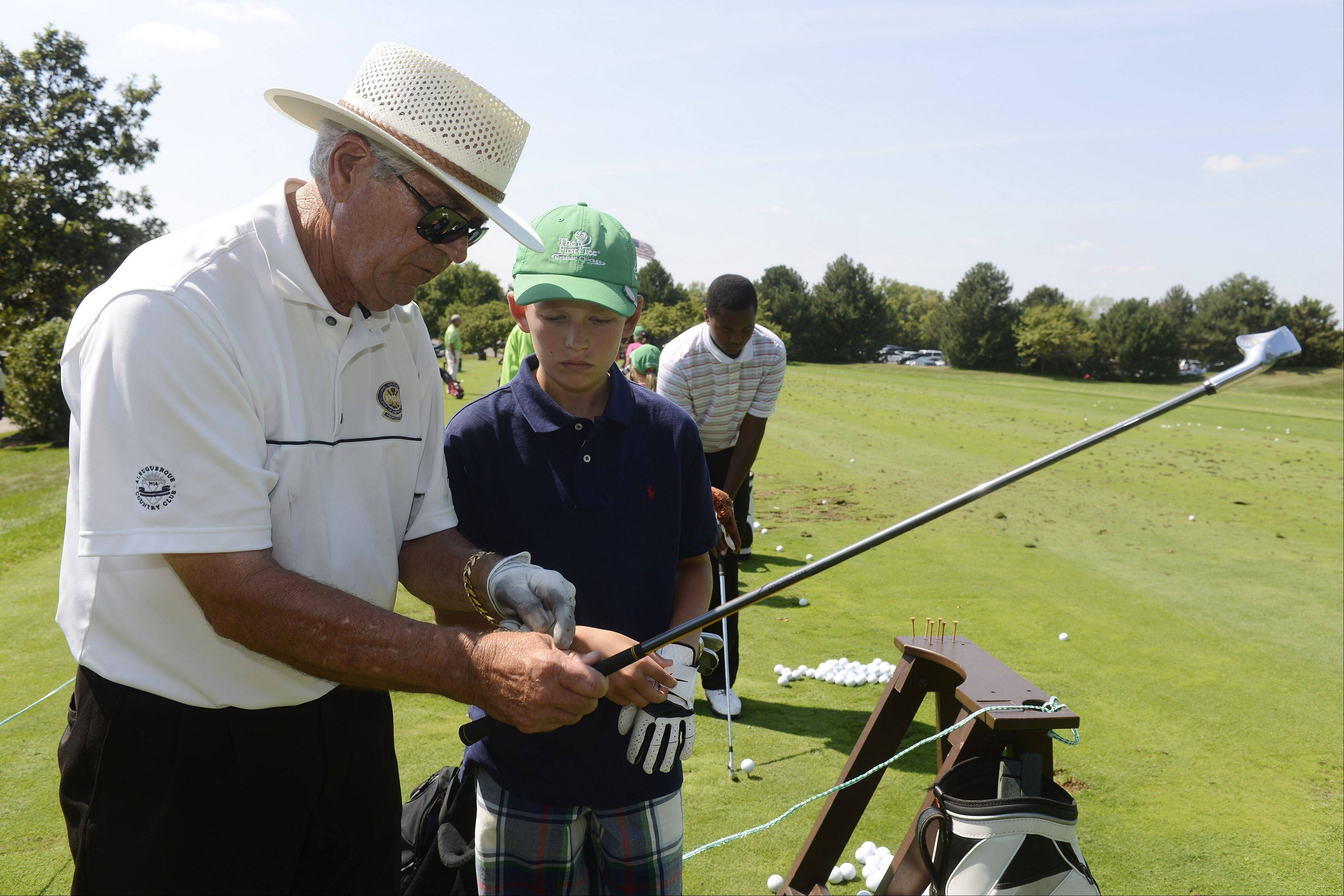 Golf teaching assistant Stan Ferguson works with Jarrett Lovitz, 11, of Gurnee during the First Tee golf event at Ivanhoe Club near Mundelein. First Tee uses the game of golf to provide education programs that build character. Thirteen kids were rewarded for their good choices with a special day at Ivanhoe.