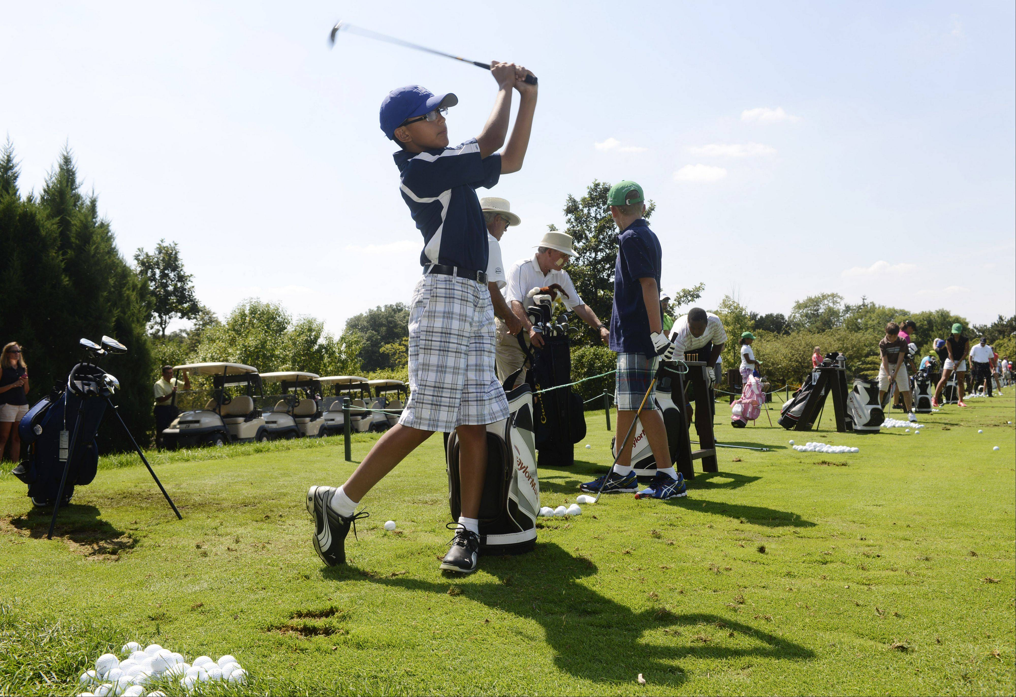 Daniel Bedon, 11, of Chicago practices his swing on the driving range during the First Tee golf event at Ivanhoe Club near Mundelein. First Tee uses the game of golf to provide education programs that build character. Thirteen kids were rewarded for their good choices with a special day at Ivanhoe.